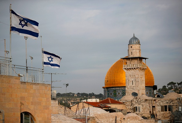 Israeli flags fly near the Dome of the Rock in the Al-Aqsa mosque compound on December 5, 2017.                 The EU's diplomatic chief Federica Mogherini said that the status of Jerusalem must be resolved  through negotiations , as US President Donald Trump mulls recognising the city as the capital of Israel.
