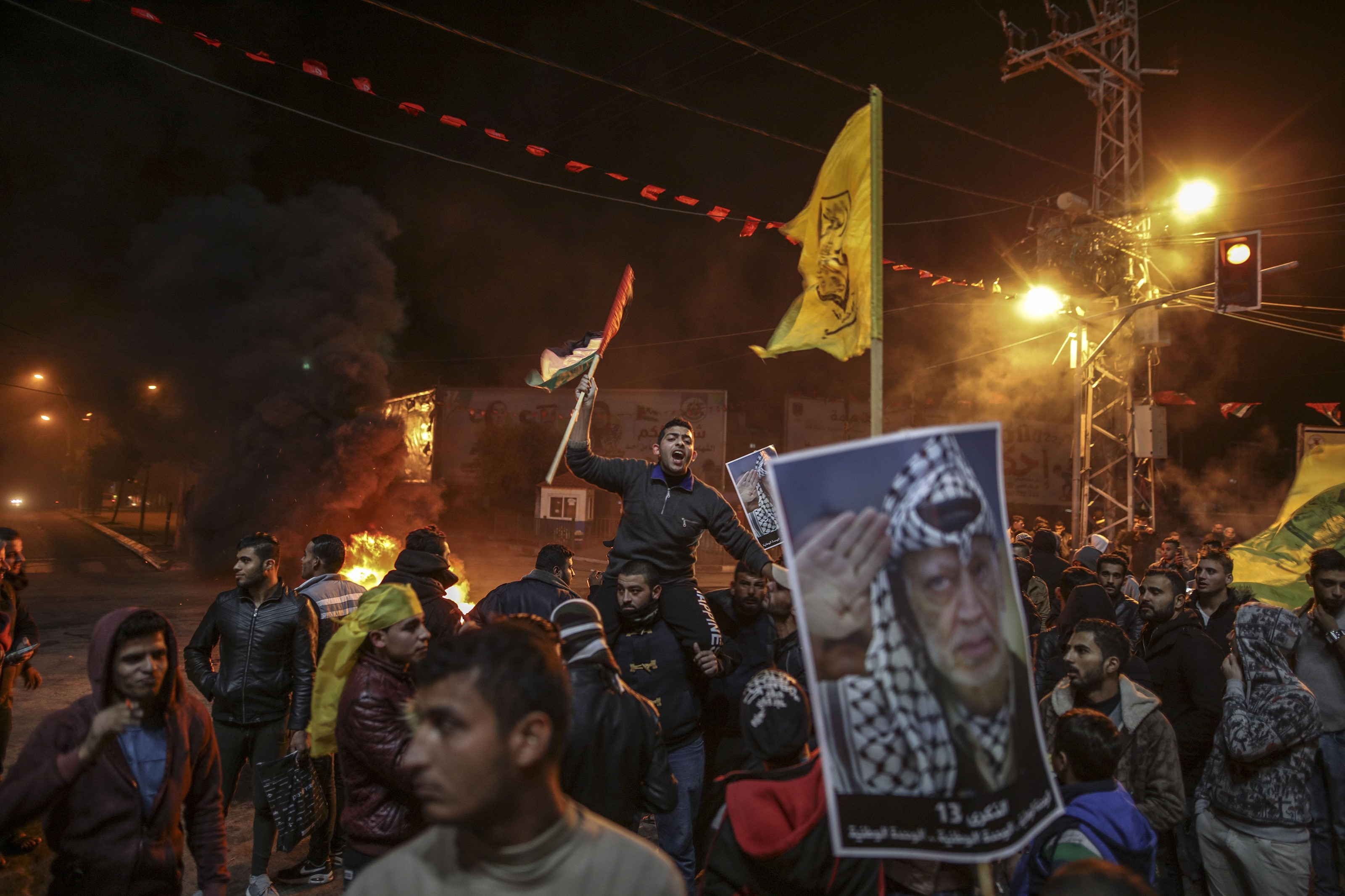 Demonstrators burn tyres, shout slogans and hold the posters of Palestinian leader Yasser Arafat during a protest against the US President Donald Trump's recognition of Jerusalem as Israel's capital, in Gaza City, Gaza on Dec. 07, 2017.