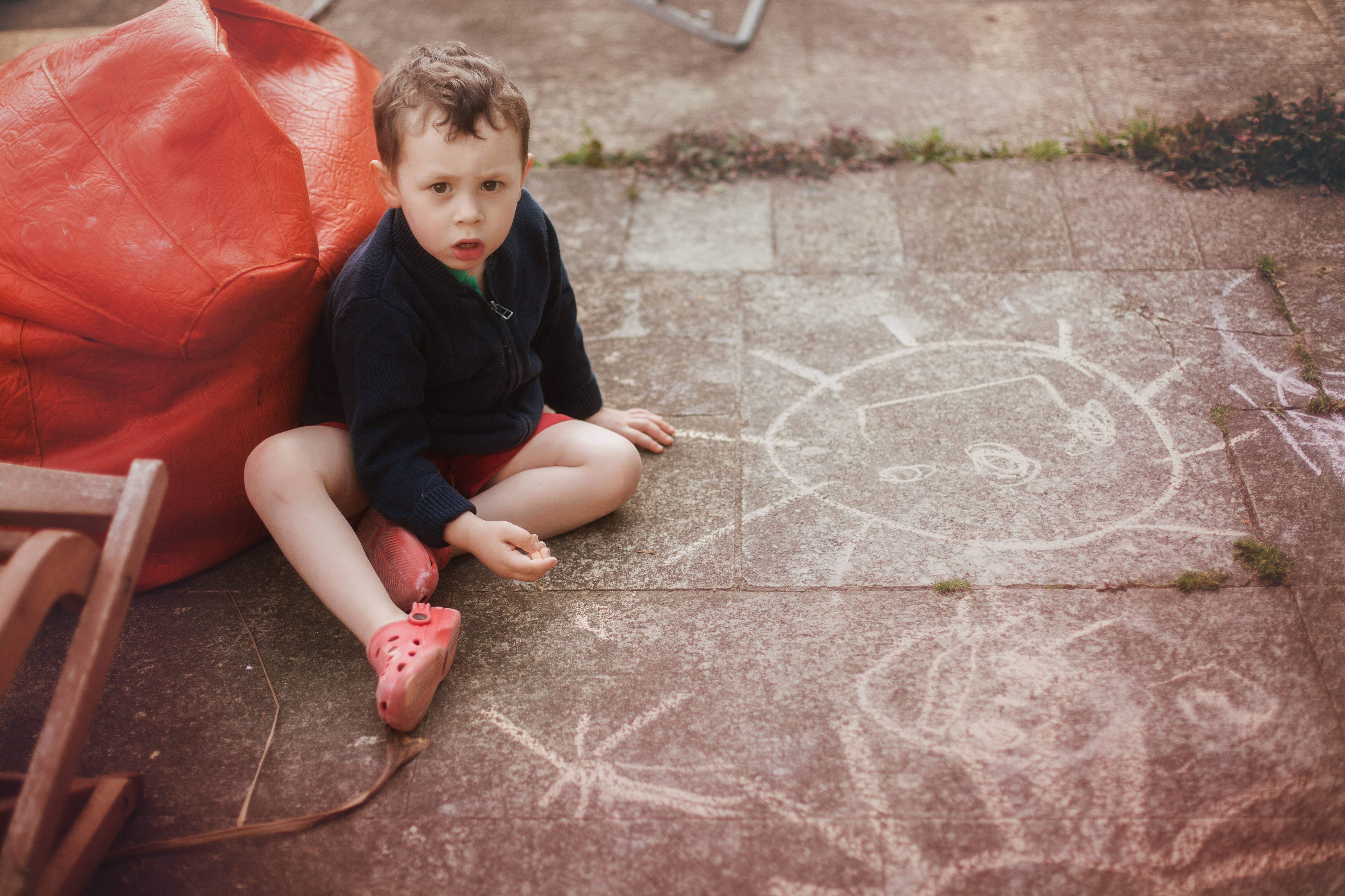 little boy drawing with chalk at the floor