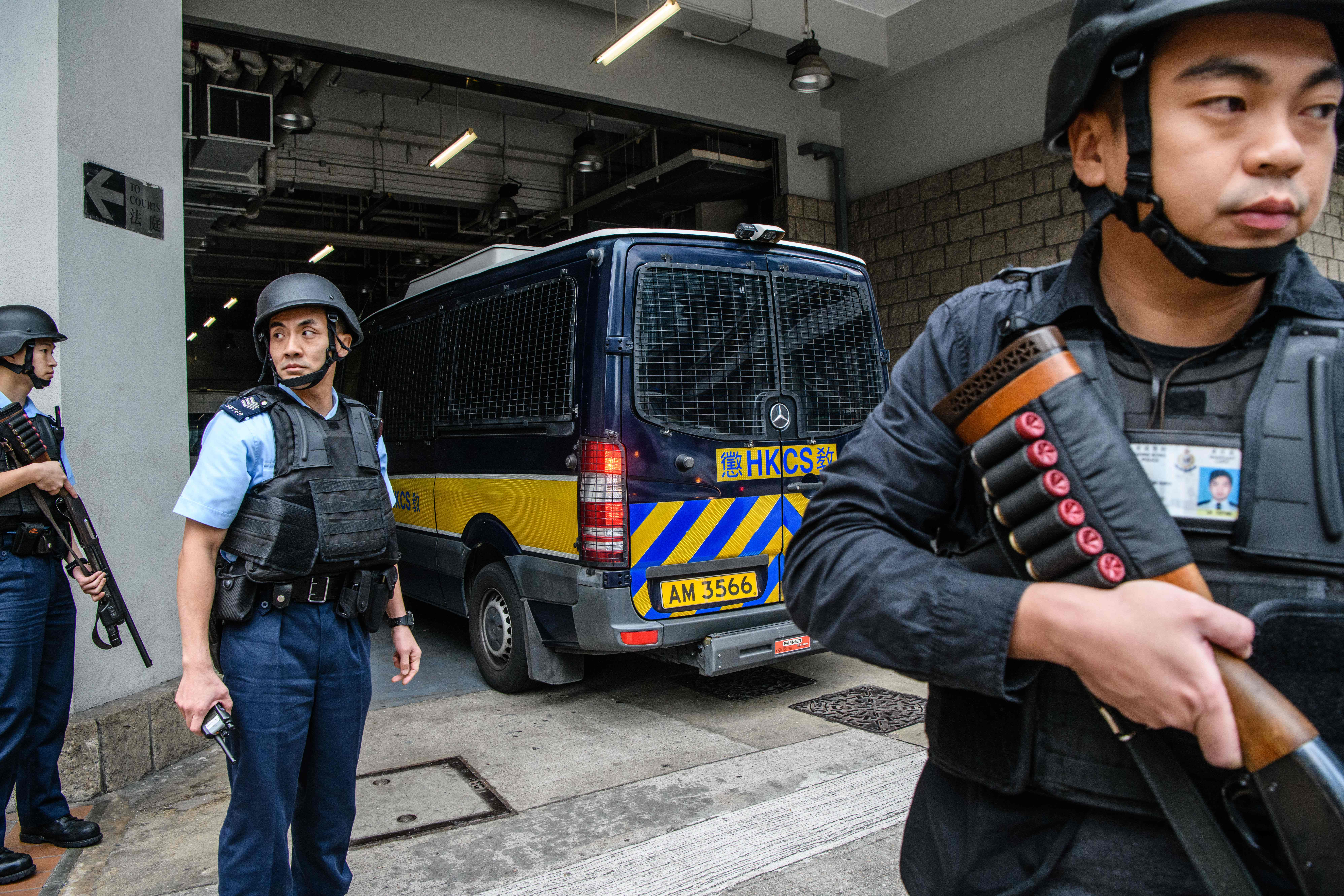 Armed police stand guard as police vehicles accompany a prison van transporting British banker Rurik Jutting outside the High Court for an appeal hearing in Hong Kong on December 12, 2017.
