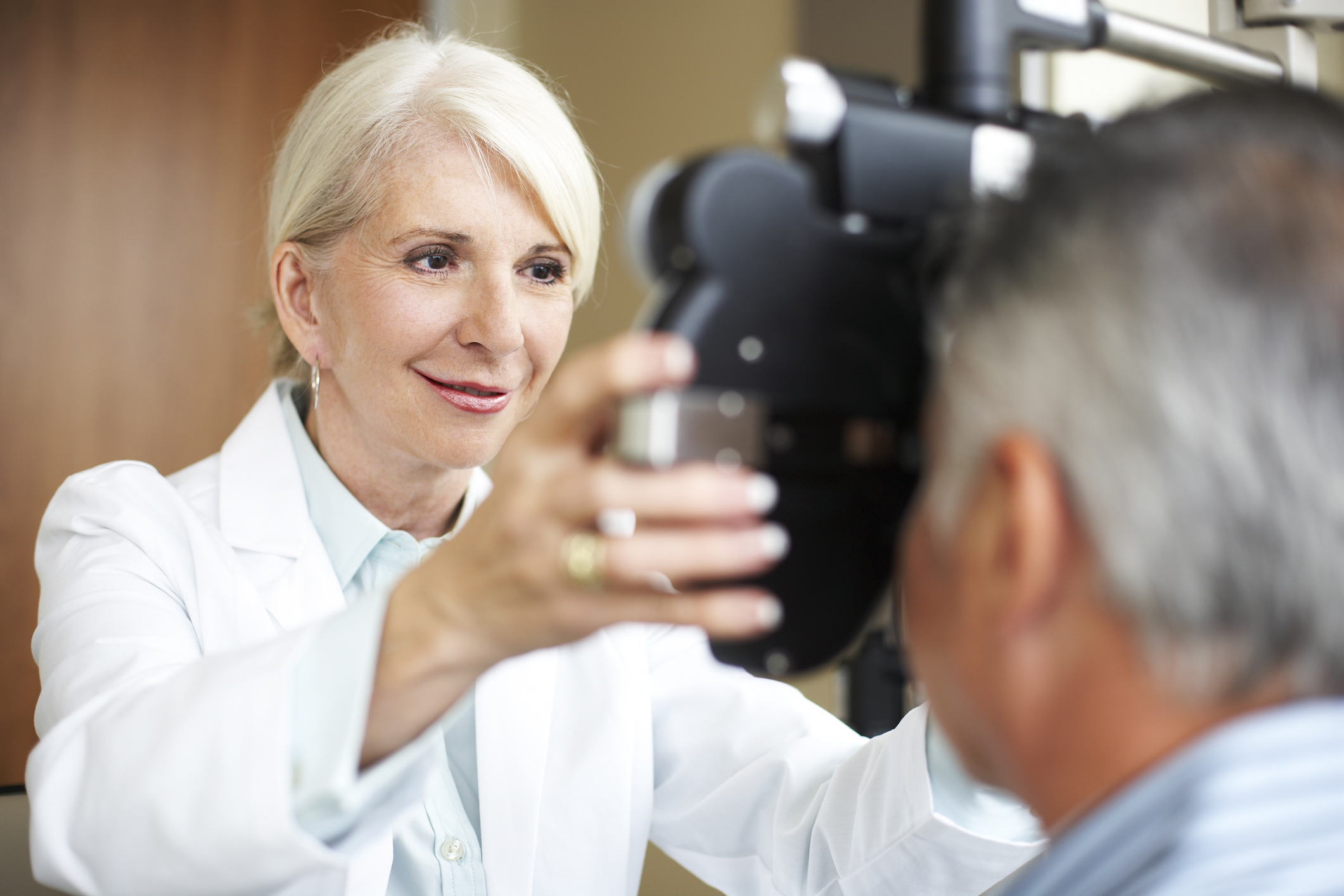 A senior female opthamologist uses a phoroptor to check a mature man's eyes.