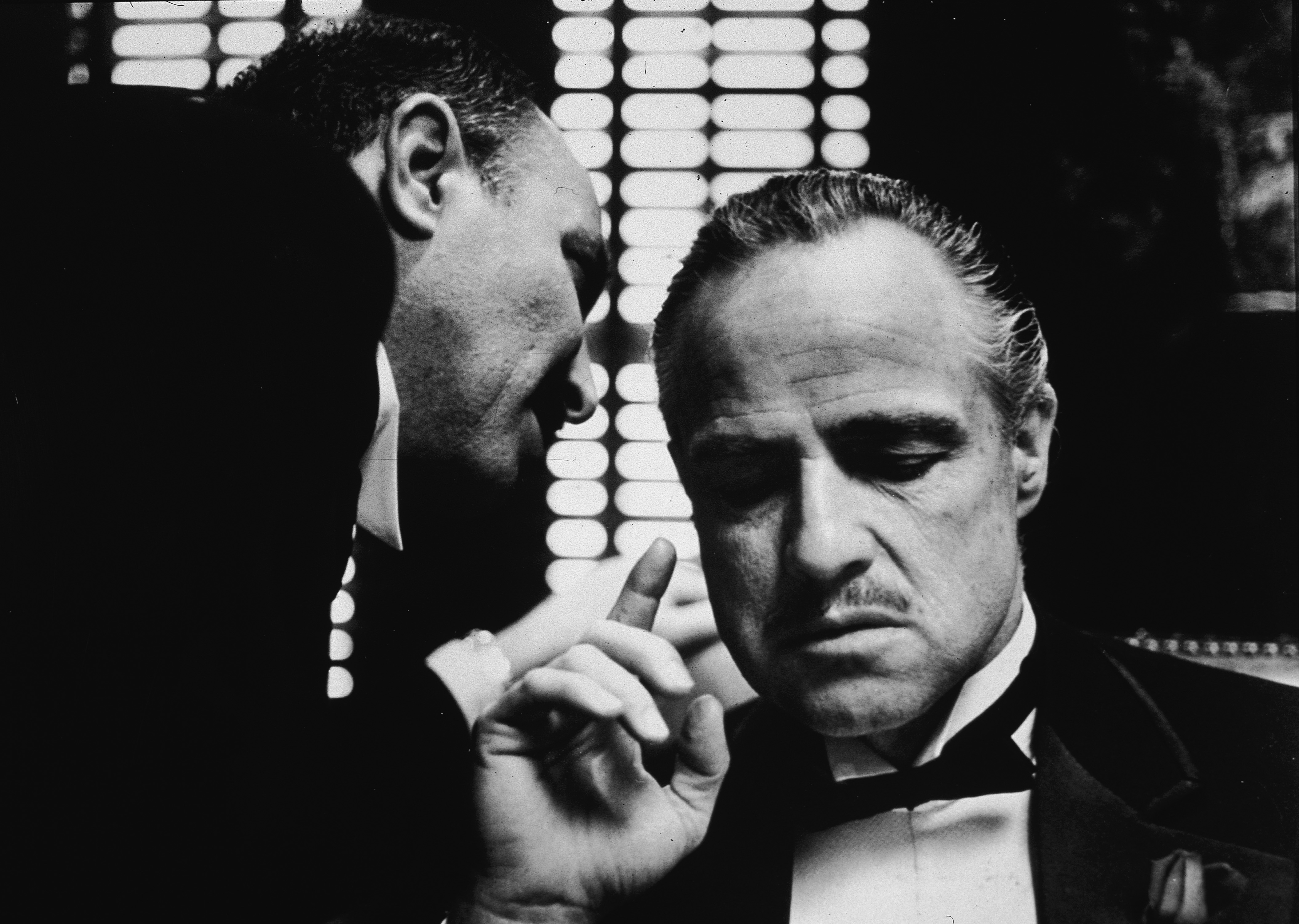 American actor Marlon Brando listens as an unidentified actor speaks close to one ear in a still from the film, 'The Godfather,' directed by Francis Coppola, 1972