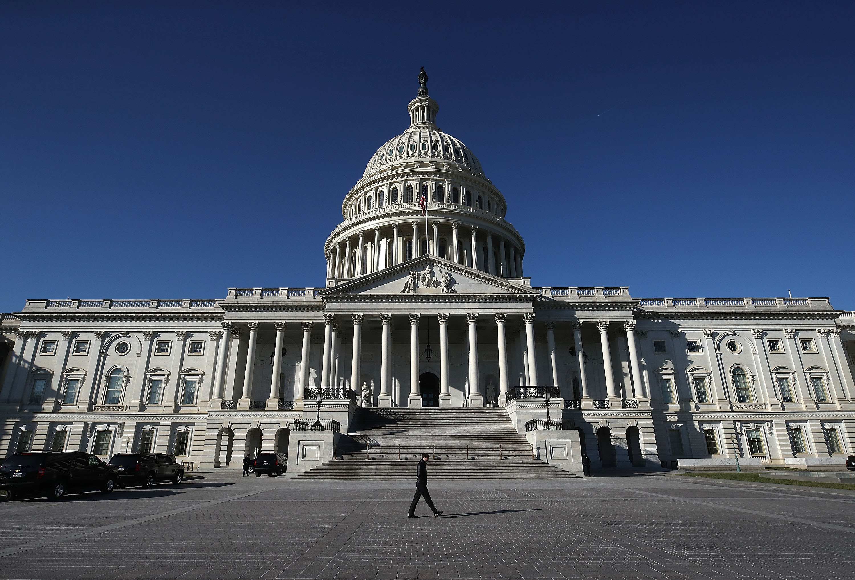 A pedestrian walks past the U.S. Capitol as congressional lawmakers work on a deal to fund the government and avert a shutdown by midnight Friday, on December 21, 2017 in Washington, DC.