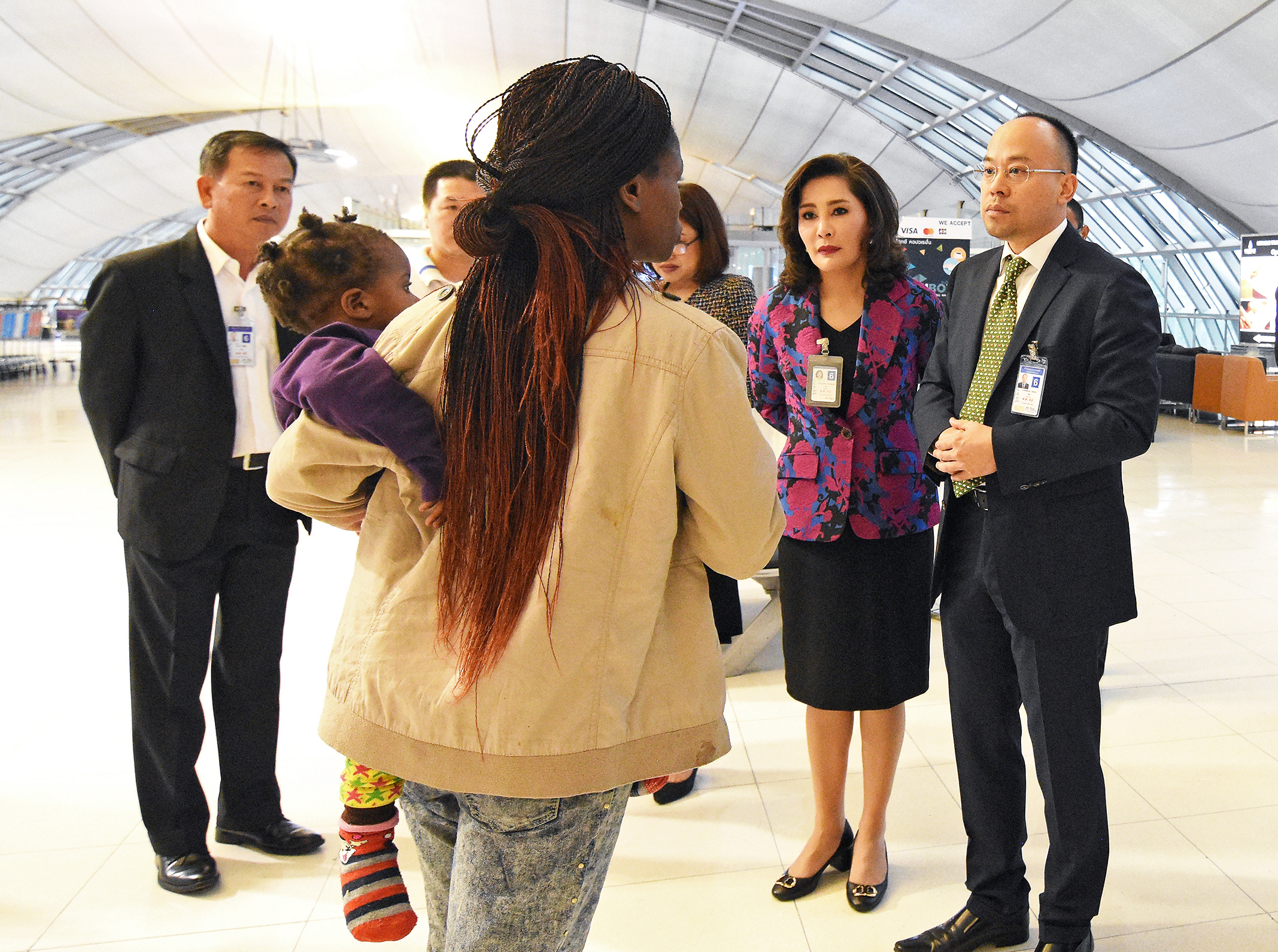 epa06408006 Thai airport officials talk to members of a Zimbabwean family that has been stranded for three months at Suvarnabhumi International Airport in Samut Prakan province, on the outskirts of Bangkok, Thailand, 27 December 2017 (issued 28 December 2017). Eight people of a family including four young children from Zimbabwe has been living in the Suvarnbhumi airport for three months as they awaiting their asylum pending process for refugee status from the United Nation.  EPA-EFE/STR THAILAND OUT