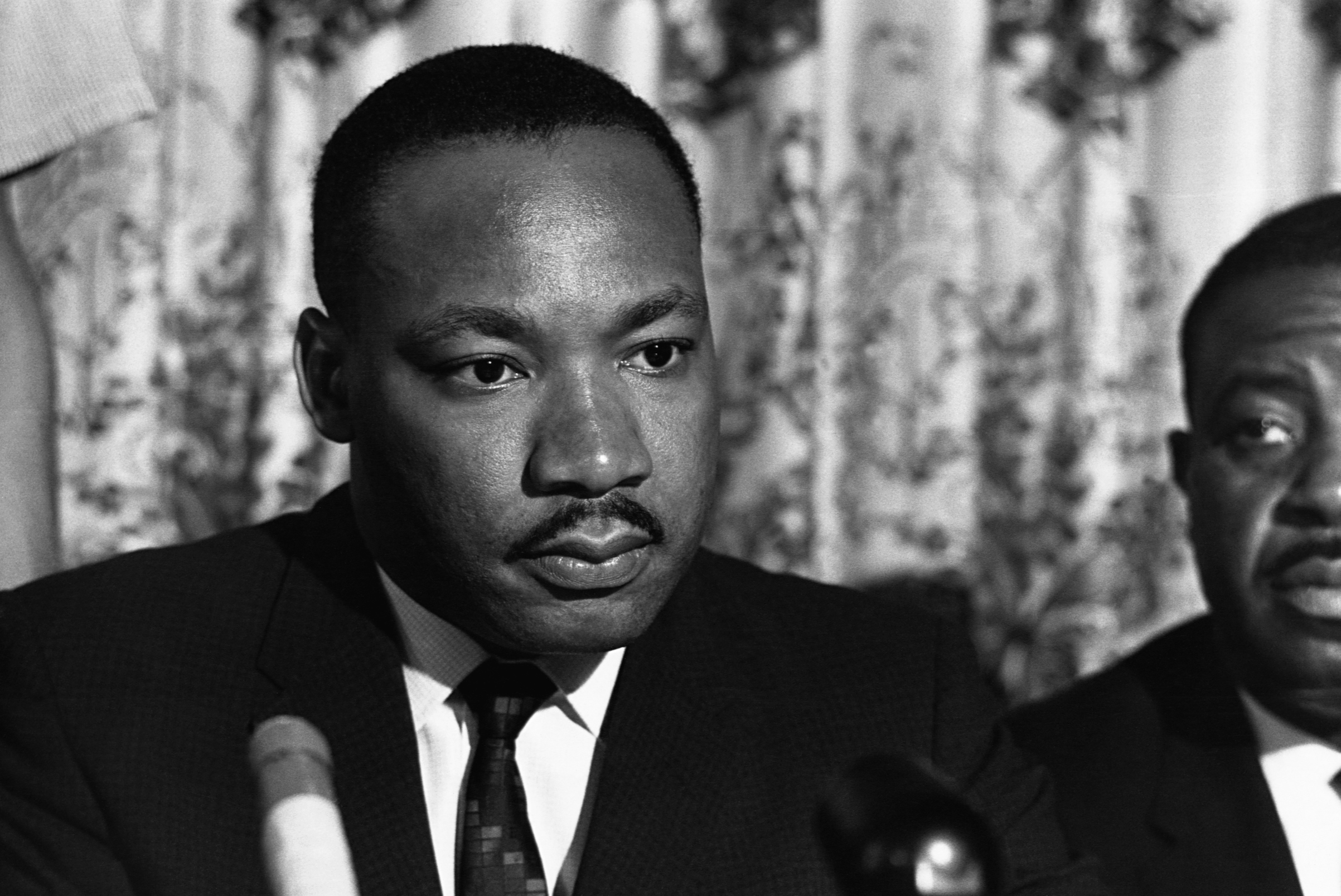 Martin Luther King, Jr. listens to a question at a news conference.