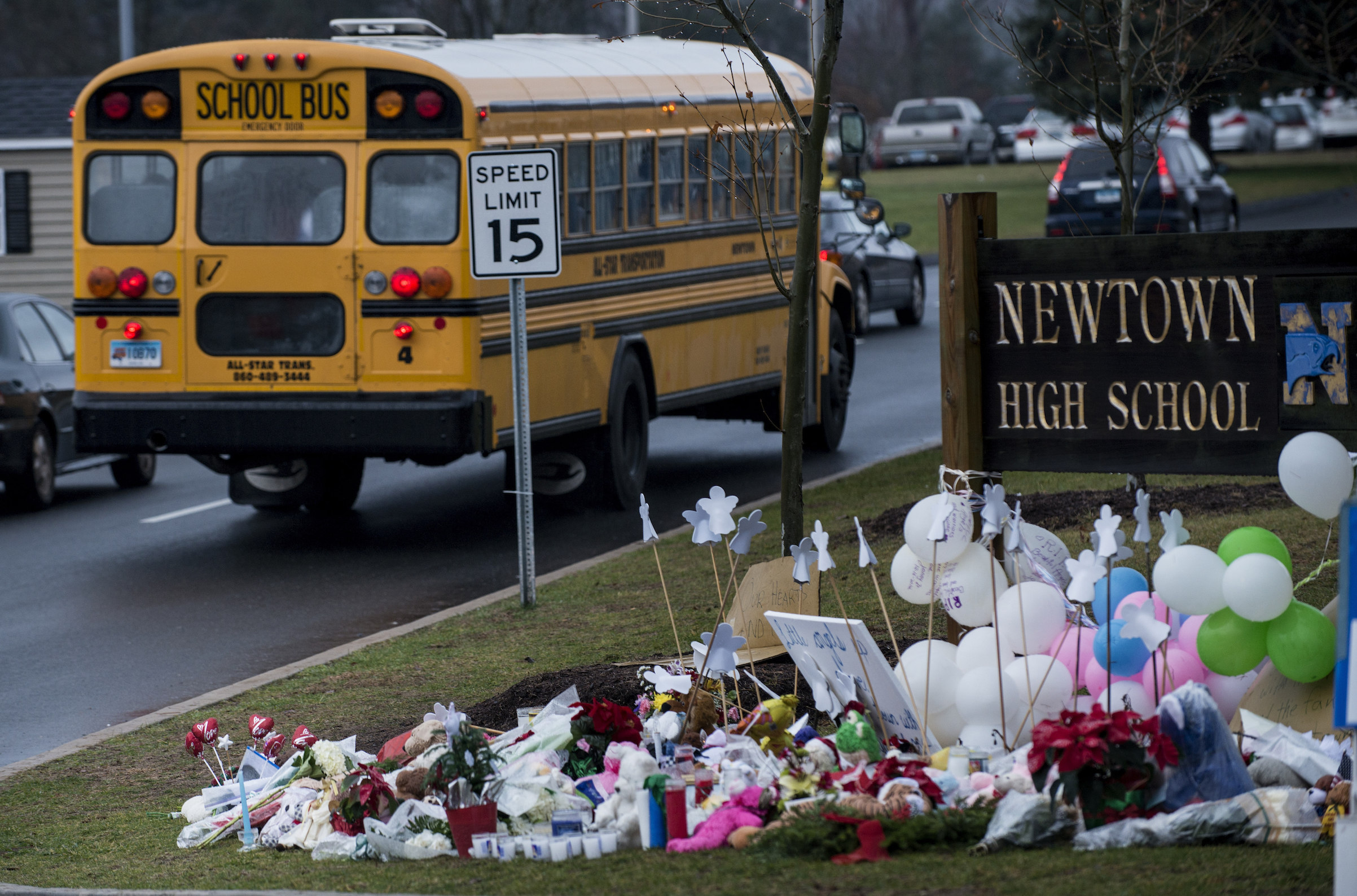 A school bus passes a makeshift memorial to the victims of the Sandy Hook Elementary School shooting as it takes students to Newtown High School Dec. 18, 2012 in Newtown, Conn.
