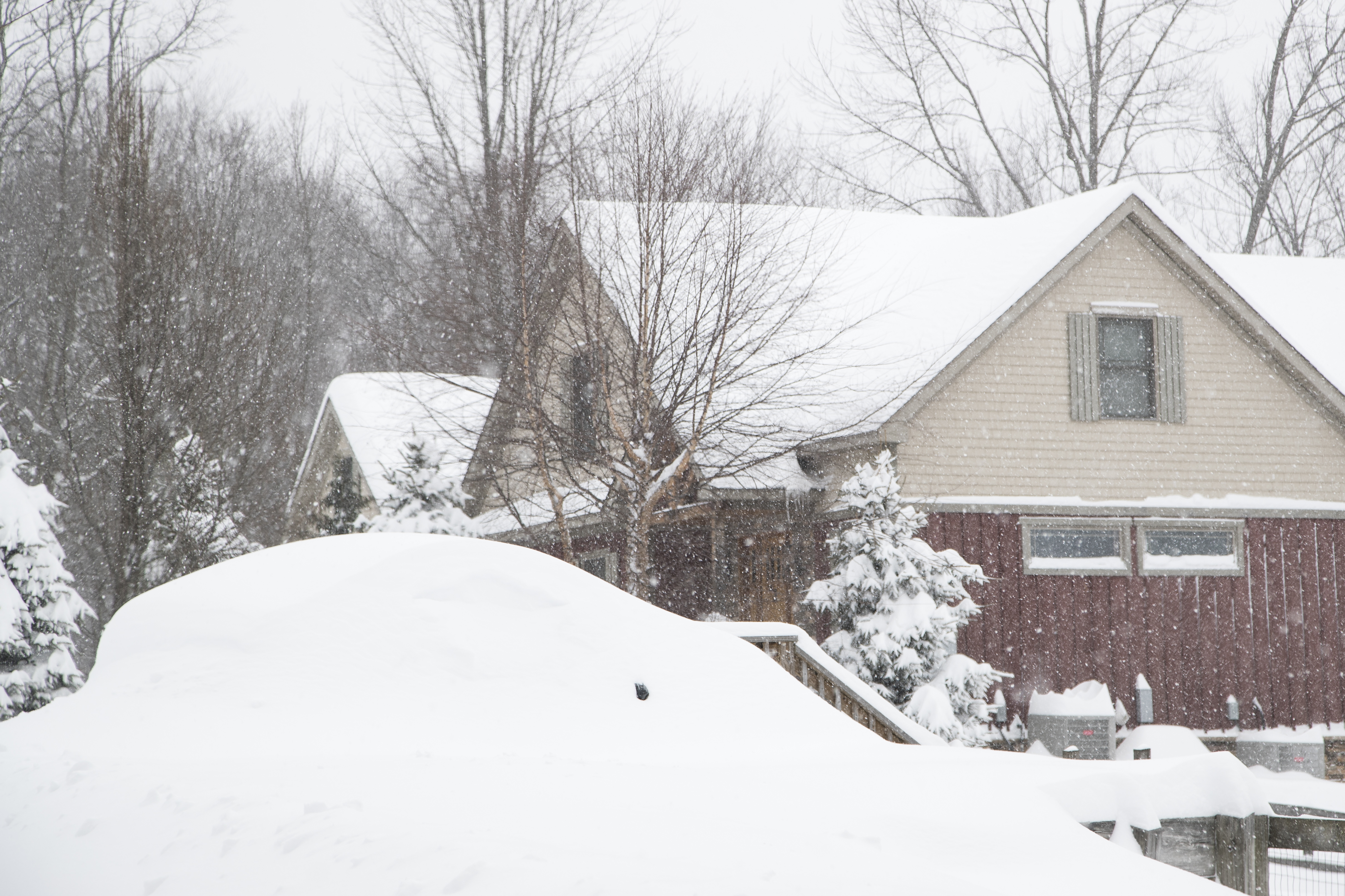 Snow covers a car (foreground) at a home in Union Dale, Pennsylvania following heavy snowfall on March 14, 2017.