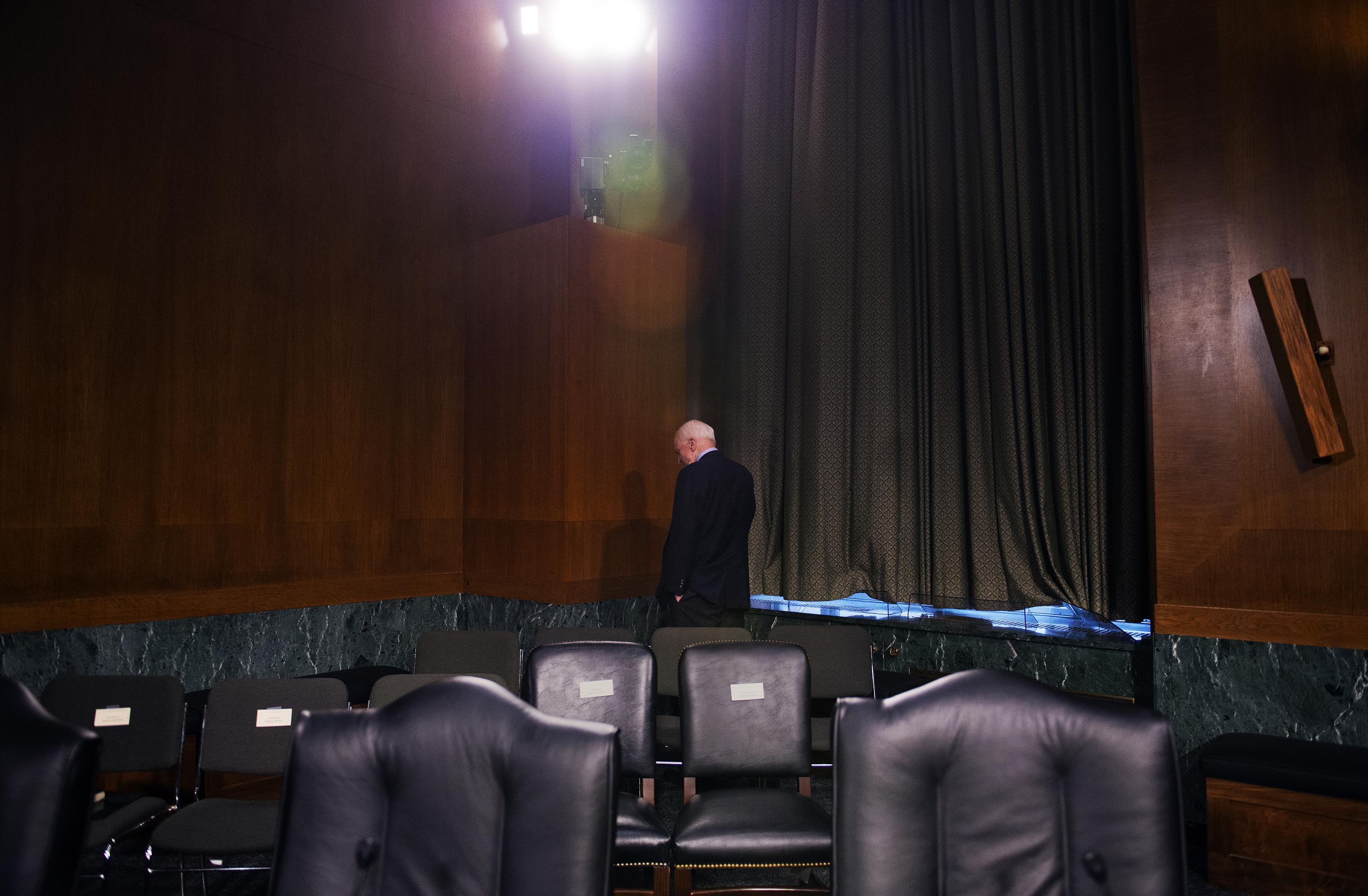 Sen. John McCain talks on the phone before a Senate Armed Services Committee hearing.