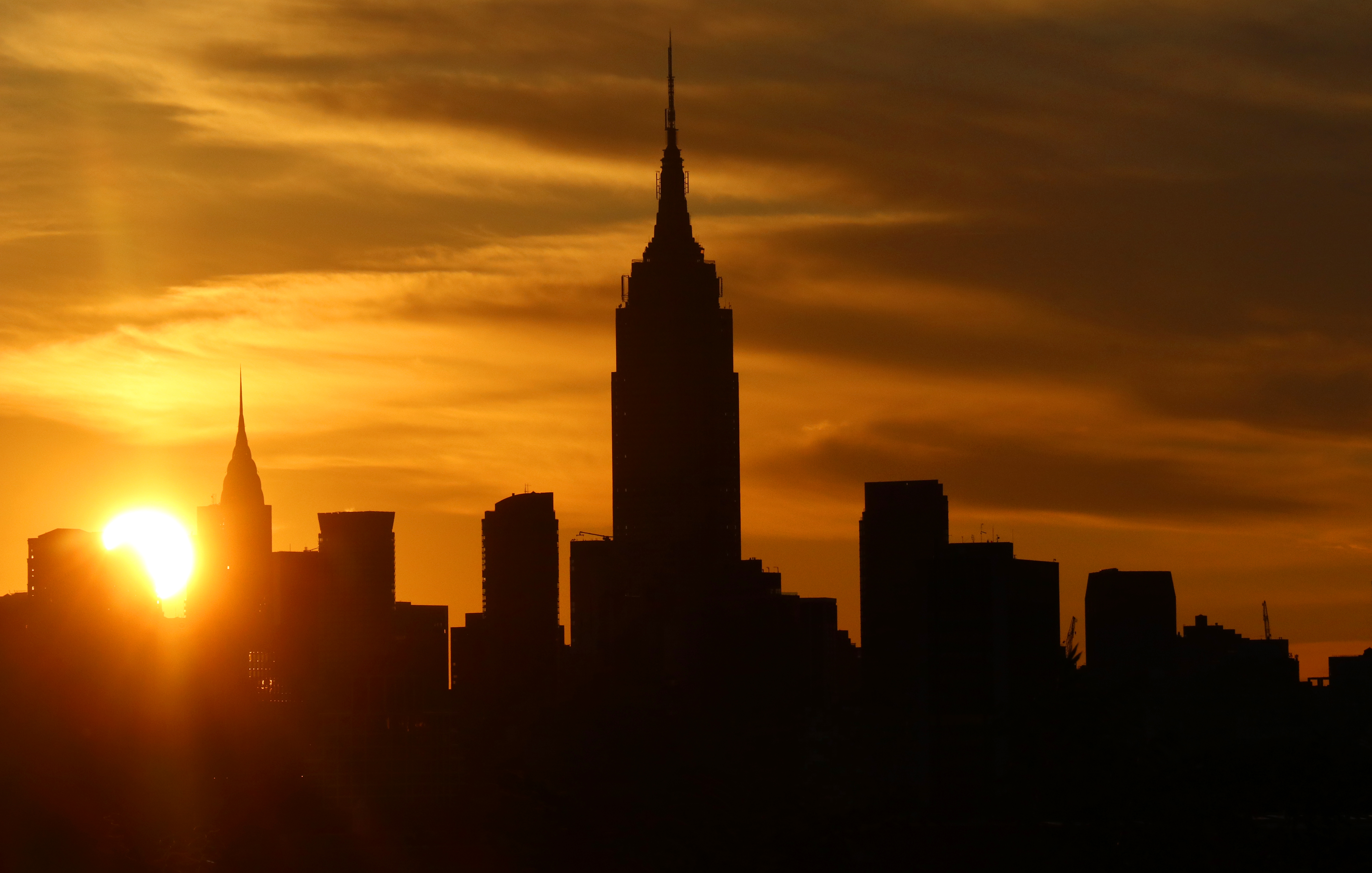 The sun rises behind midtown Manhattan and the Empire State Building in New York City on September 2, 2017, as seen from Jersey City, New Jersey.