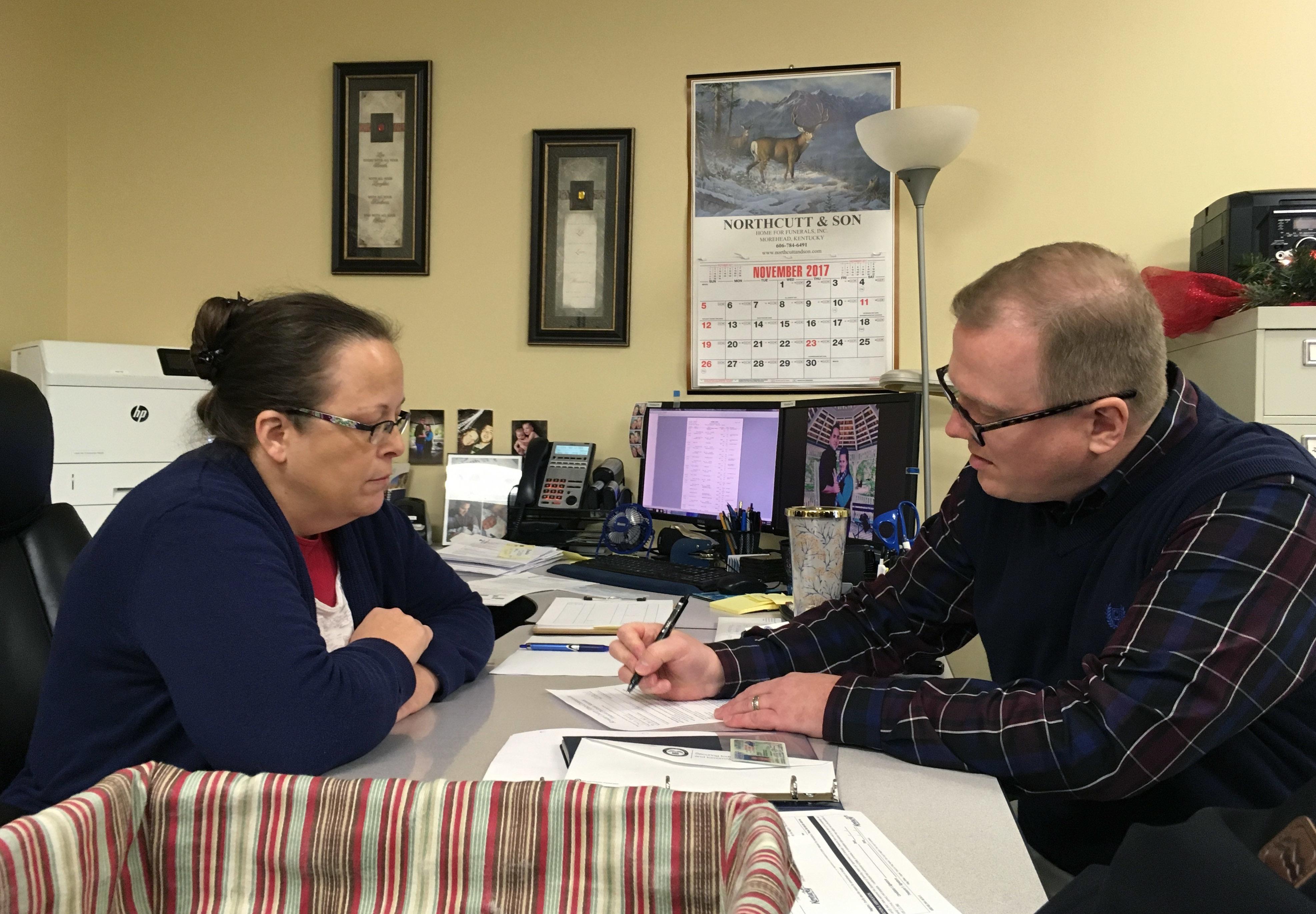 David Ermold, right, files to run for Rowan County Clerk in Kentucky as Clerk Kim Davis, left, looks on