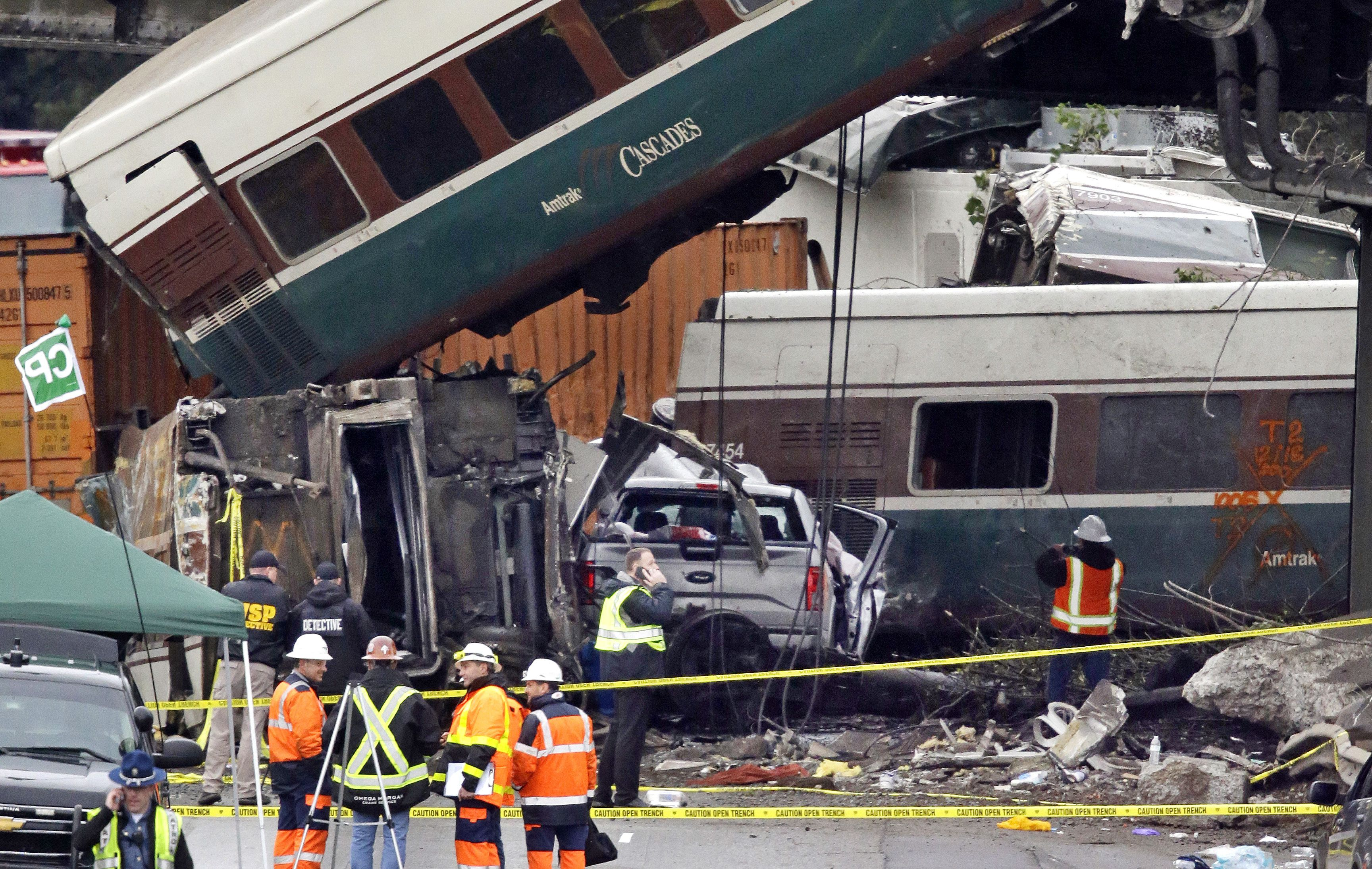 Cars from an Amtrak train that derailed above lay spilled onto Interstate 5 alongside smashed vehicles, in DuPont, Wash. The Amtrak train making the first-ever run along a faster new route hurtled off the overpass Monday near Tacoma and spilled some of its cars onto the highway below, killing some people, authorities said — Shutterstock/AP