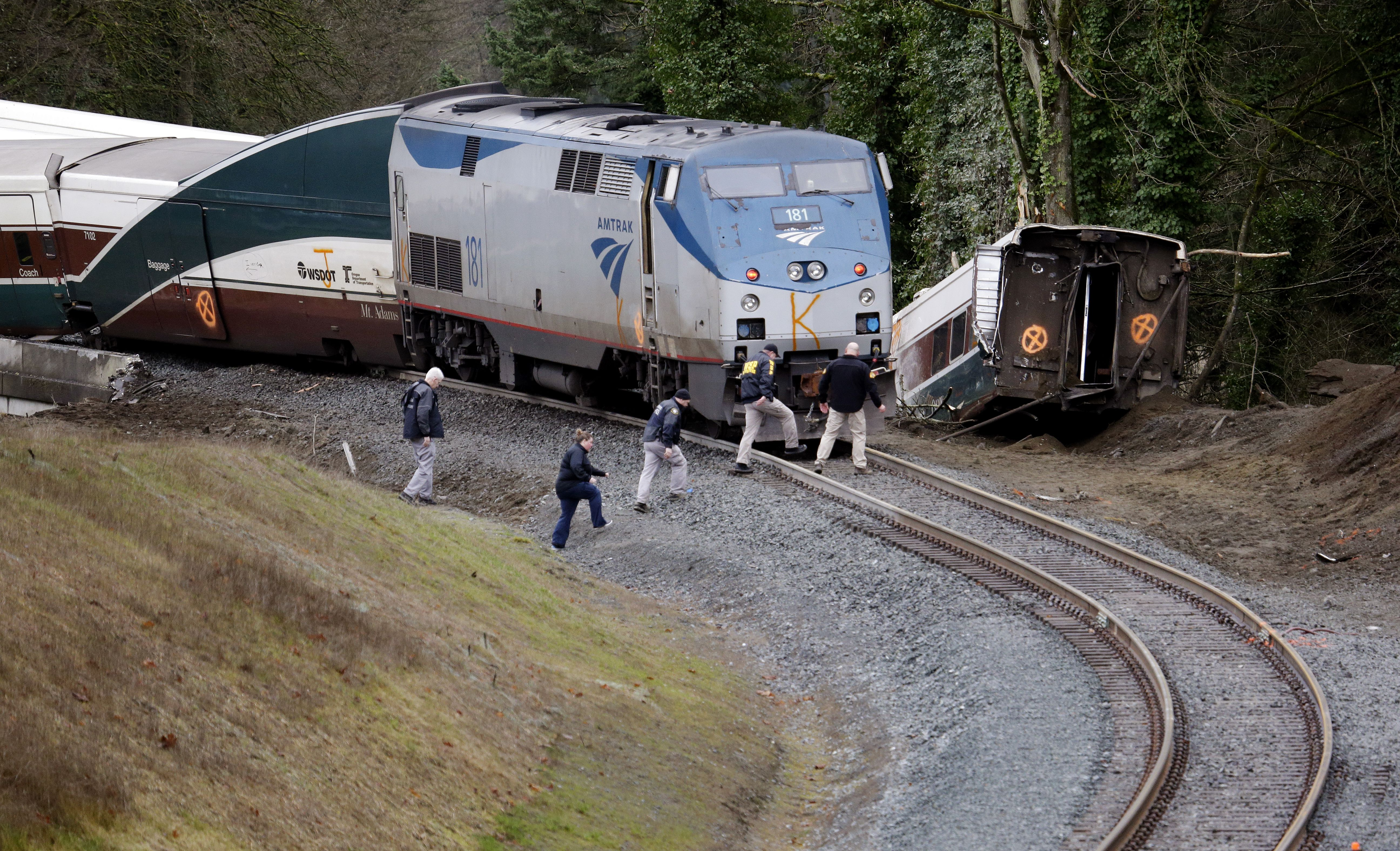Police officials walk over tracks near a curve at the back of where an Amtrak train derailed above Interstate 5, in DuPont, Wash — Shutterstock/AP