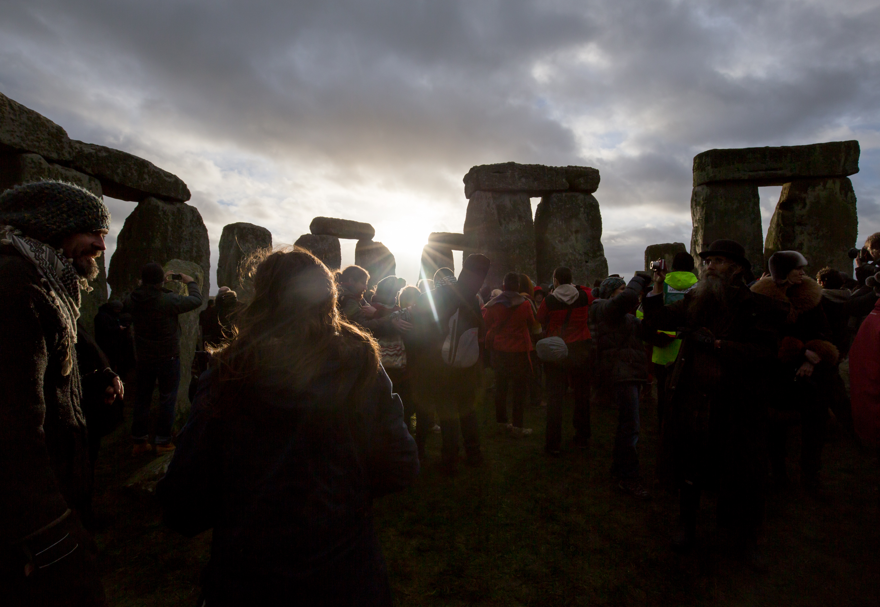 The sun makes a brief appearance through clouds as druids, pagans and revelers gather in the centre of Stonehenge in Wiltshire, England for the 2015 winter solstice.