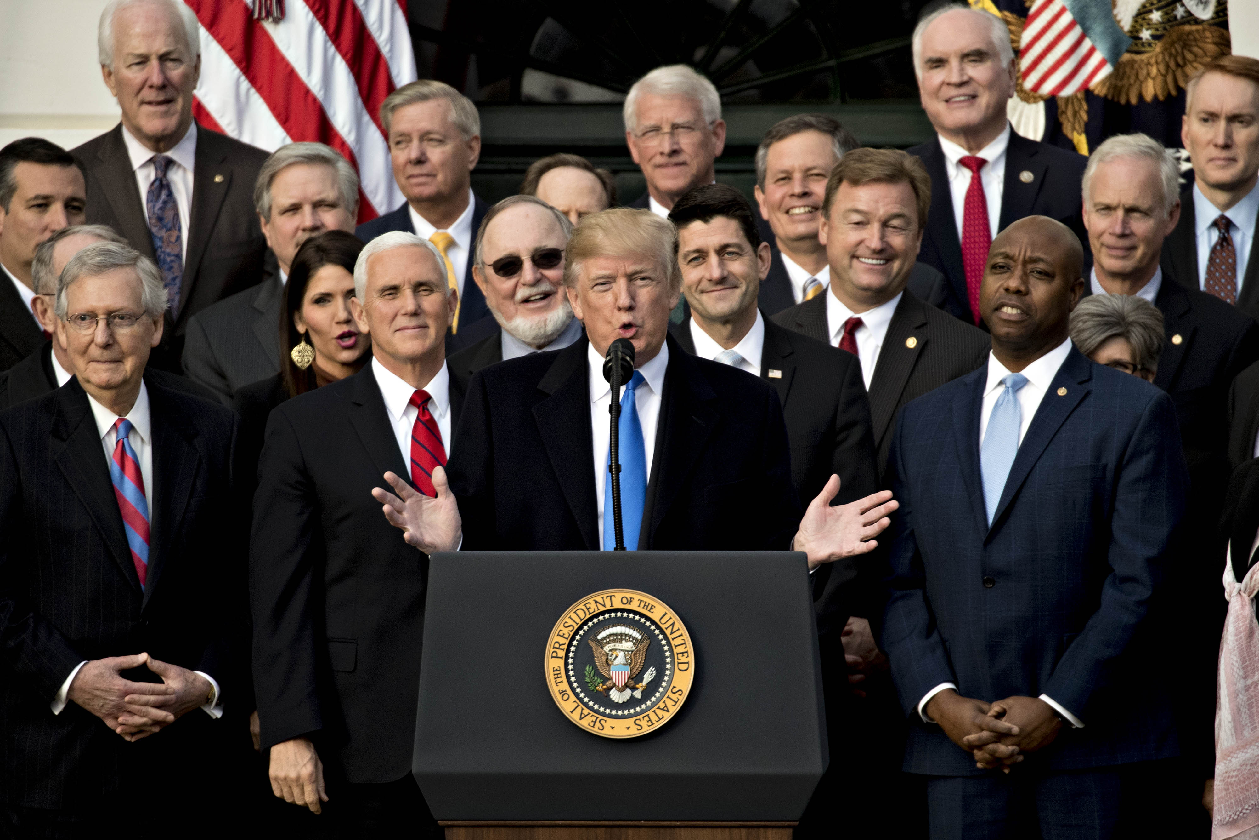 President Donald Trump, center, speaks during a tax bill passage event with Republican congressional members of the House and Senate on the South Lawn of the White House in Washington, D.C., on Dec. 20, 2017.