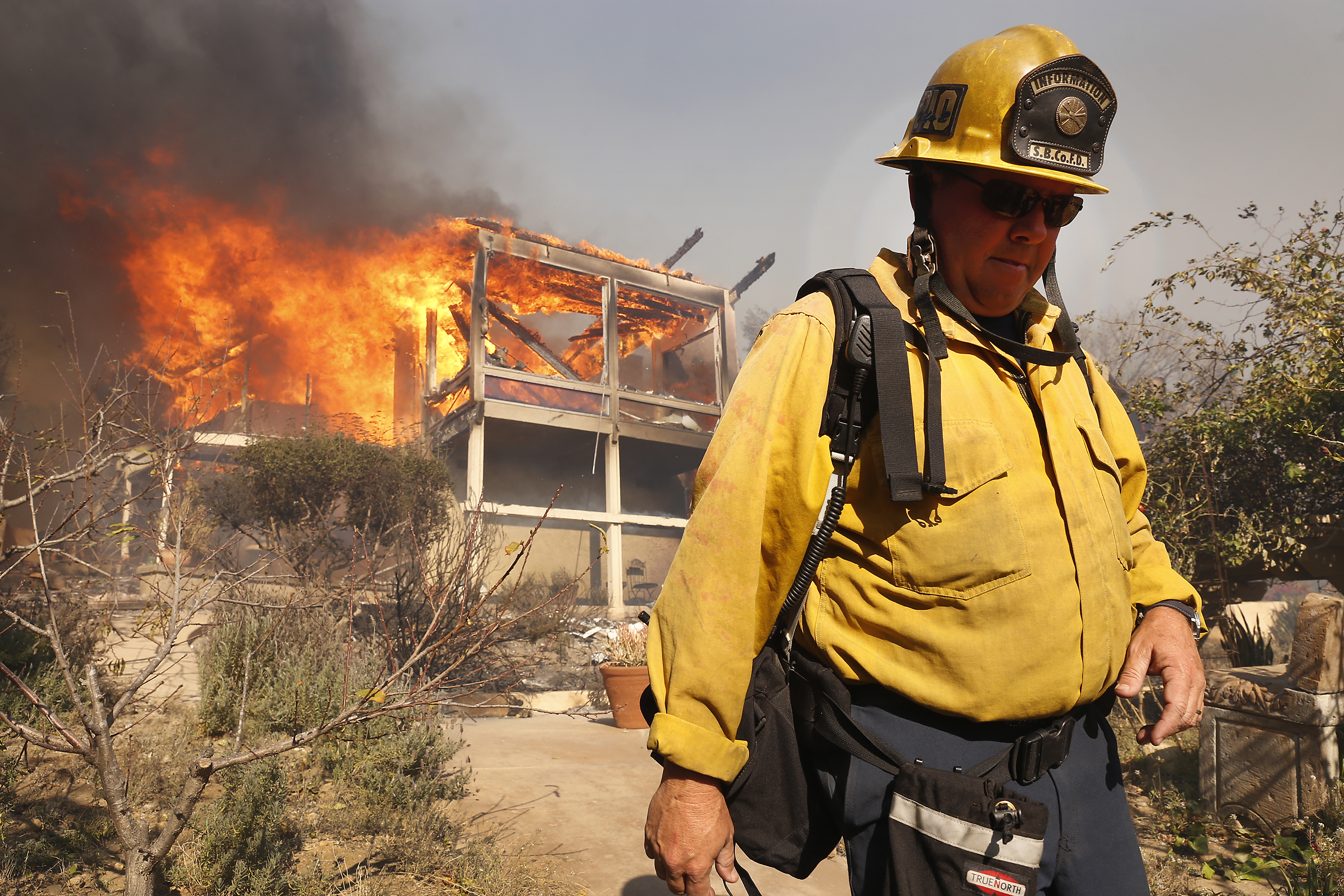 Santa Barbara PIO Mike Eliason watches as a home between Via Baja and Foothill goes up in flames Tuesday midday after the fast-moving, wind-fueled Thomas fire swept through Ventura County.