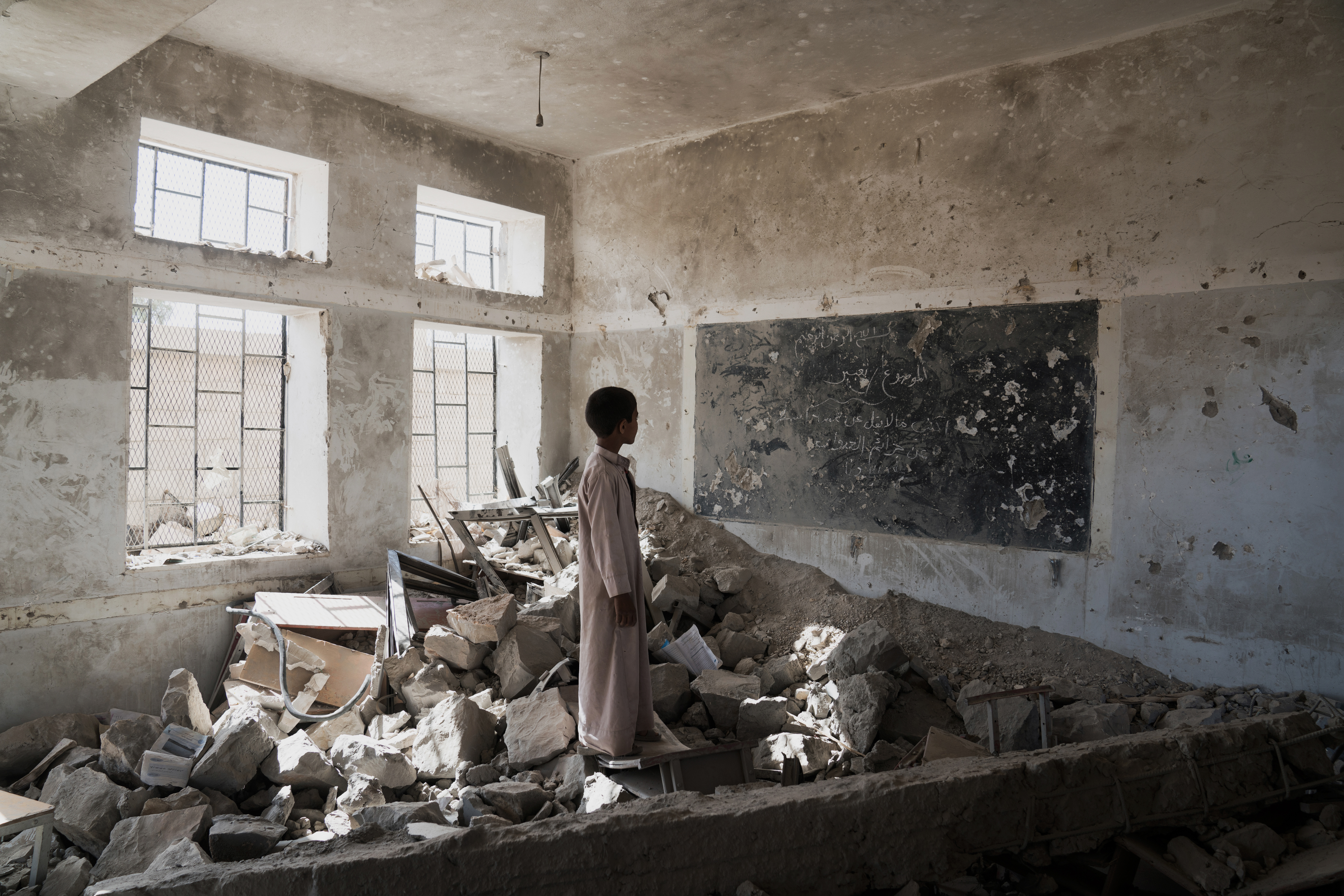 A student stands in the ruins of a classroom in Saada, Yemen, on April 24, 2017.