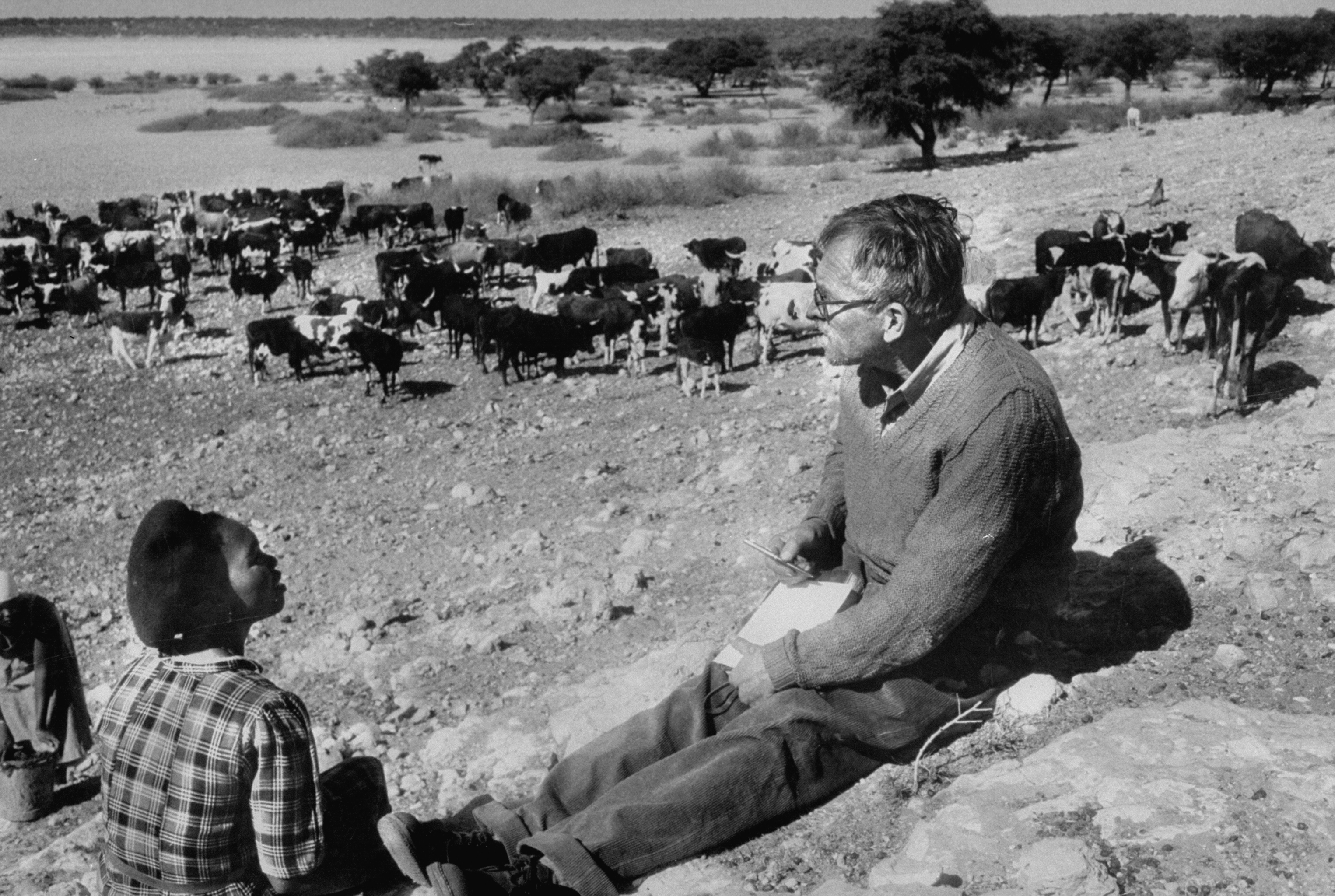 Author, Alan Paton (R) interviewing Herrero woman, Katrina Whiteman against the backdrop of the Tshani well during during his Kalahari expedition in Bechuanaland.