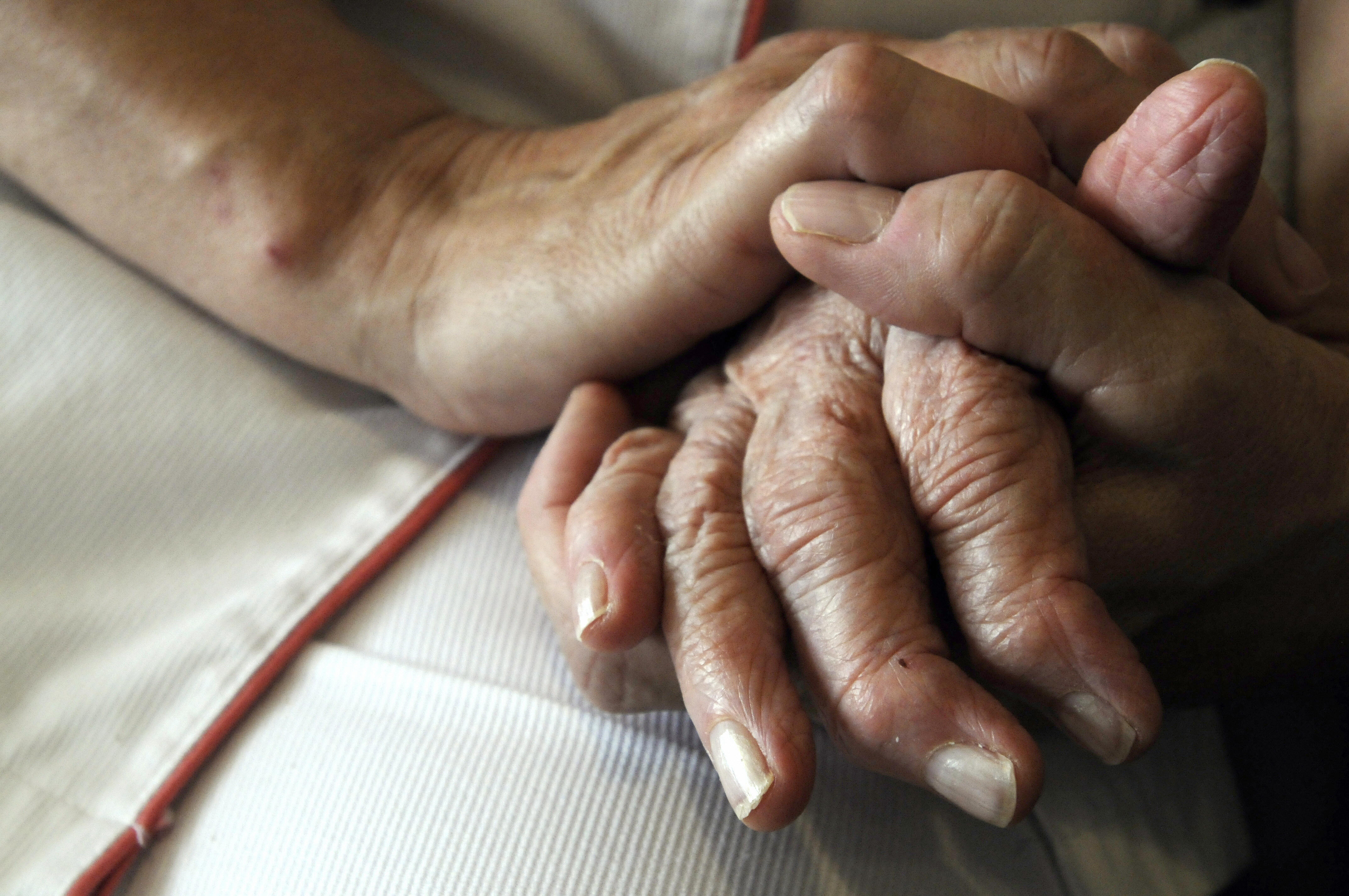 A nurse holds the hands of a person suffering from Alzheimer's disease on September 21, 2009 at Les Fontaines retirement home in Lutterbach , eastern France.