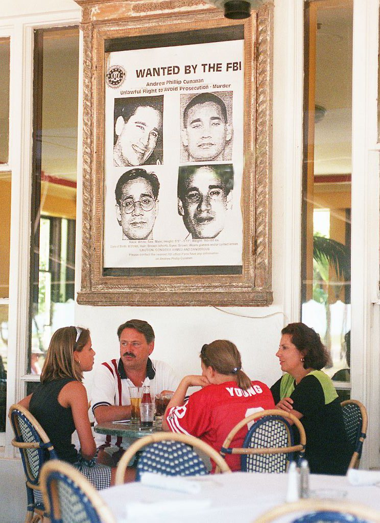 Diners at the Edgewater Hotel on Miami Beach sit under a large wanted poster of Andrew Cunanan in July 1997