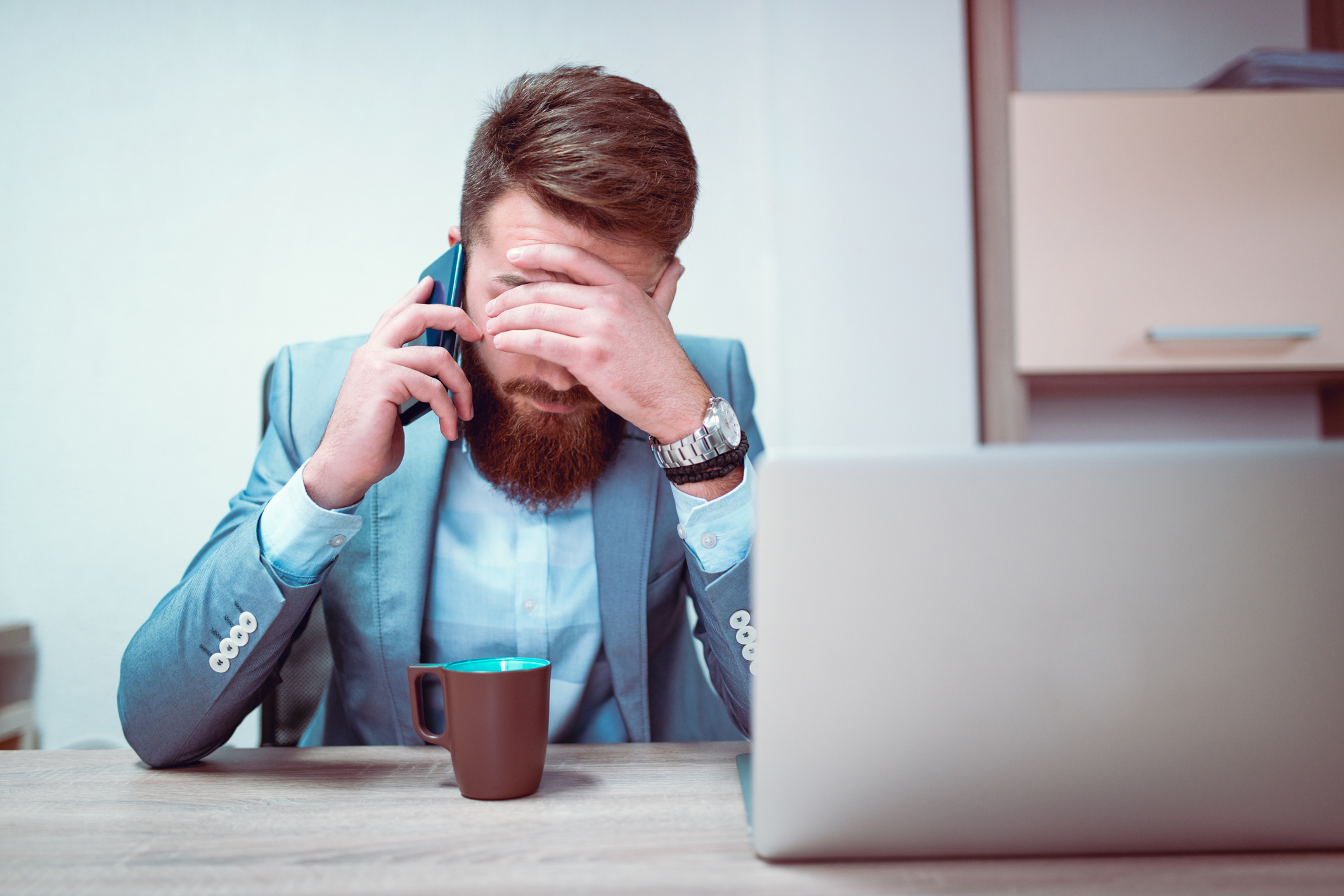 Photo of a young frustrated businessman with his hands on his face, he is exhausted and worried about his work problems. Talking on his mobile phone in front og his laptop computer and coffee mug.