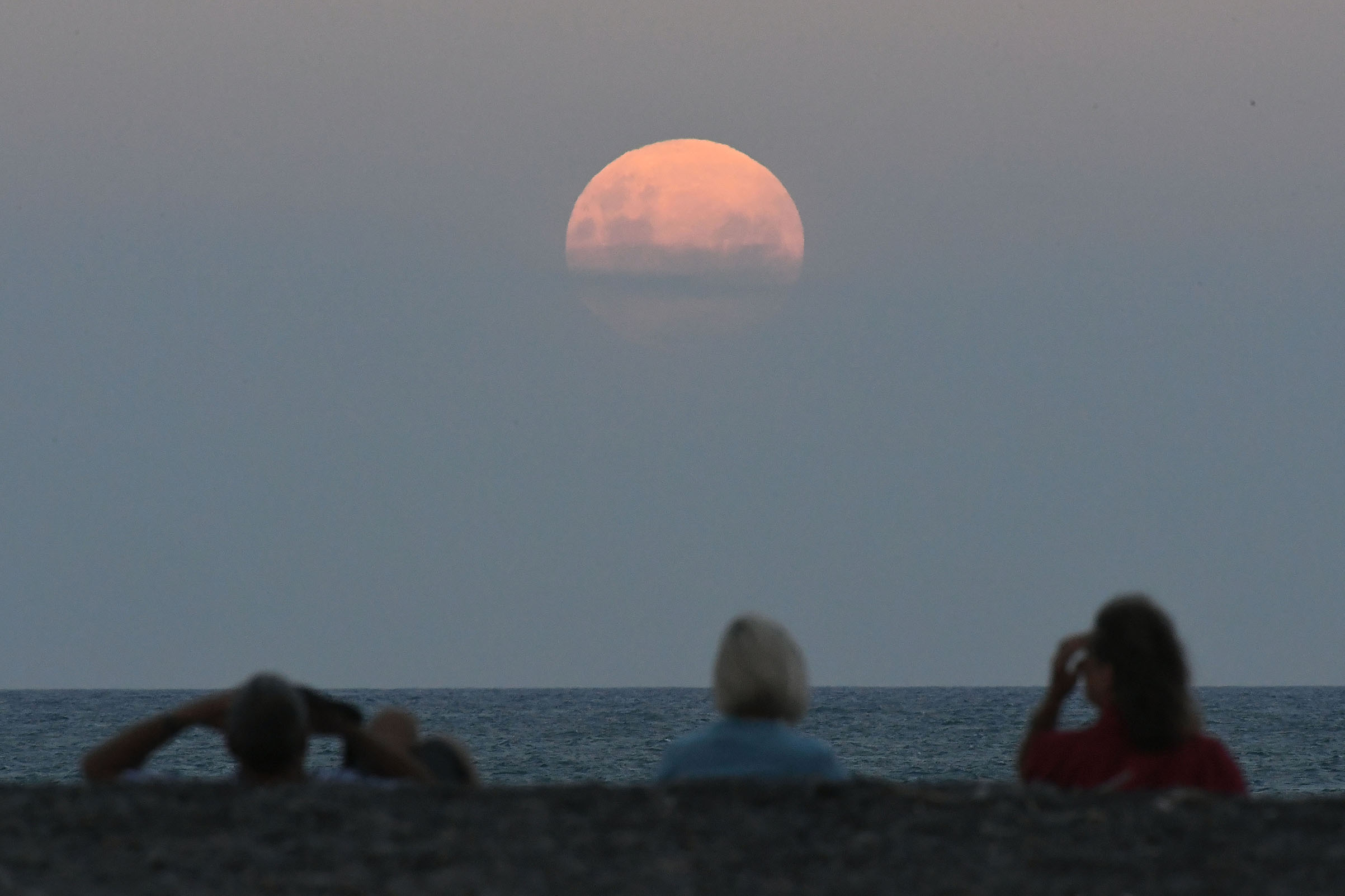 Crowds gather on the Marine Parade Beach to watch the Super Blue Blood Moon rise in Napier, New Zealand on Jan. 31, 2018.