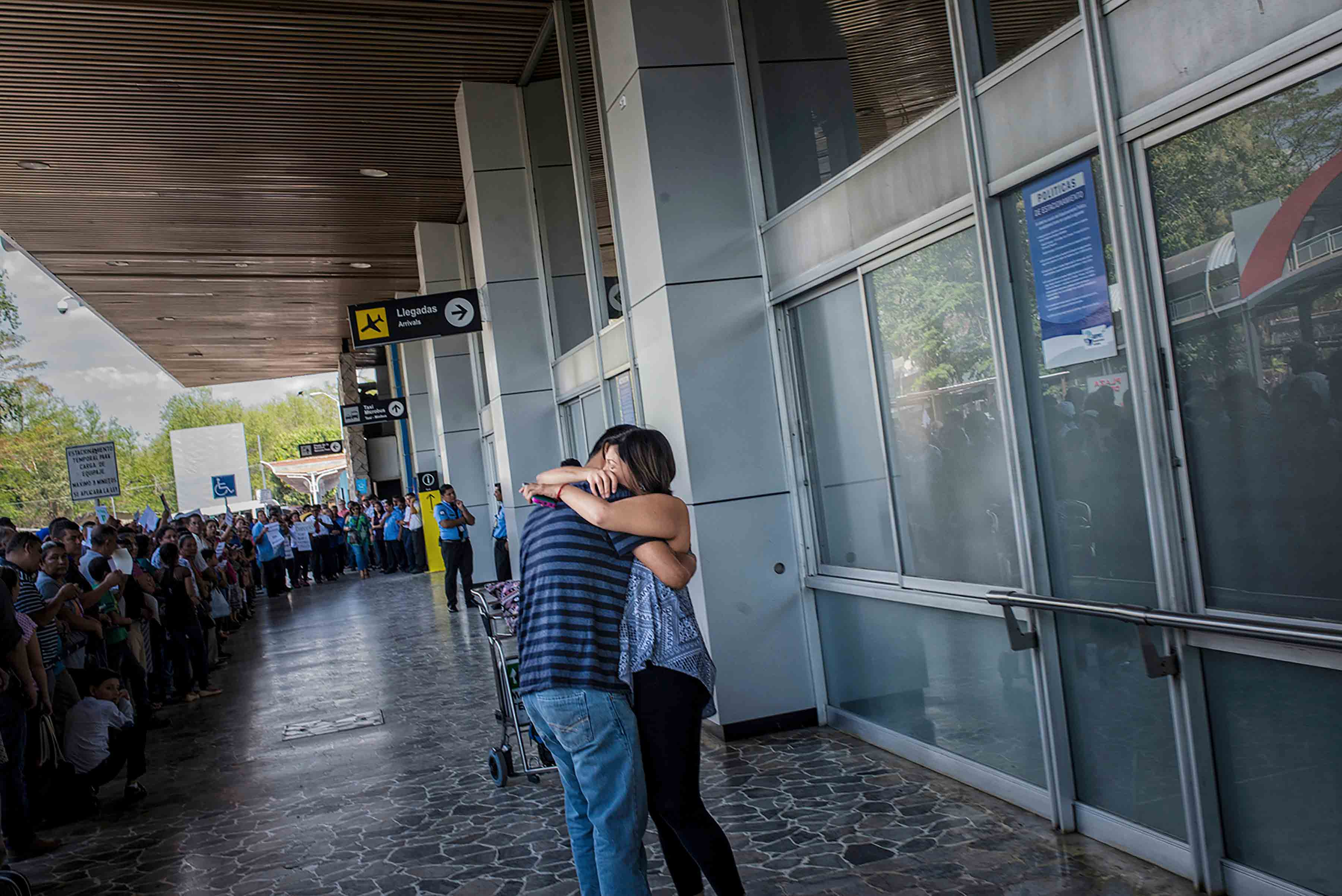 Jose Escobar hugs his wife in El Salvador for the first time since his March deportation from Texas.