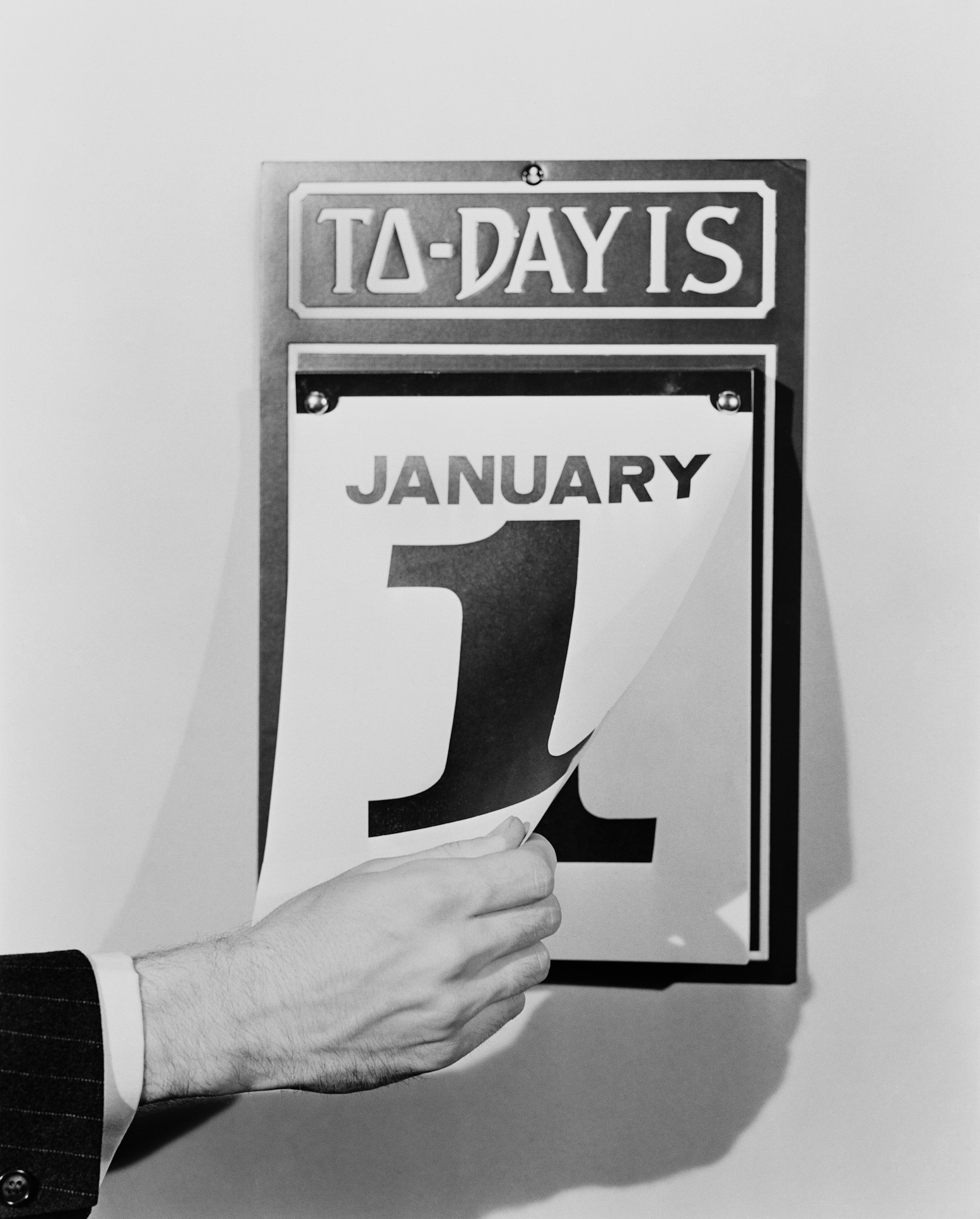 A man's hand tearing January 1 page off of daily wall calendar, circa 1930s