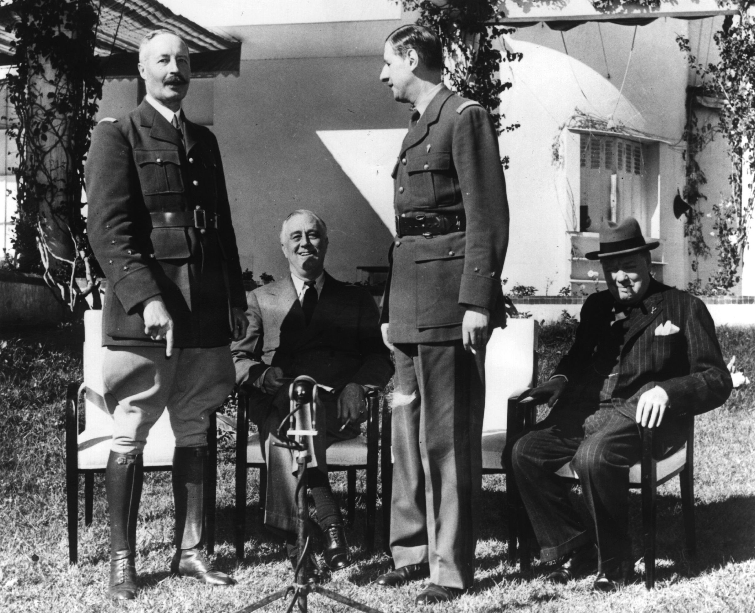 General Henri Honore Giraud and General Charles De Gaulle stand in front of American President Franklin Delano Roosevelt and British Prime Minister Winston Churchill at the Casablanca Conference.