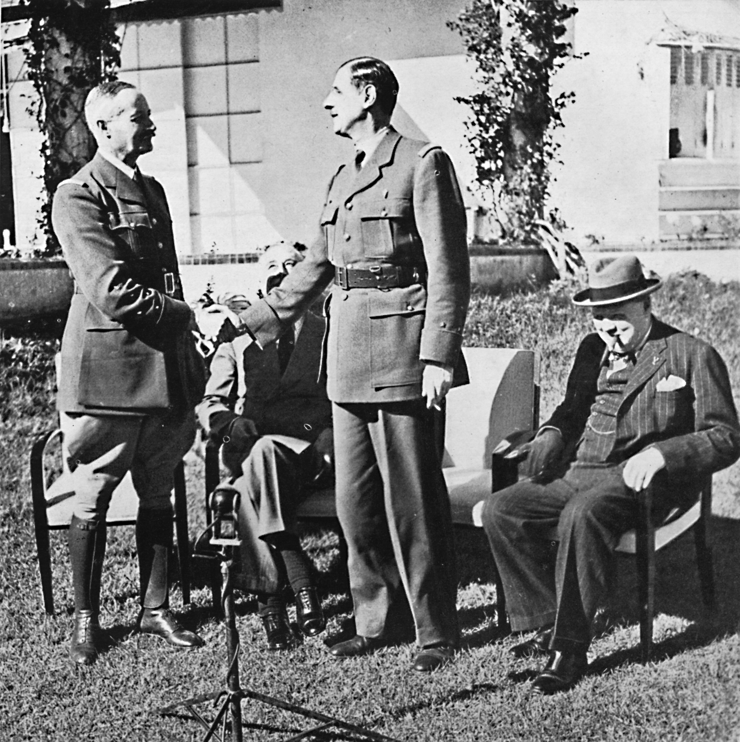 General Henri Honore Giraud and General Charles De Gaulle shake hands in front of American President Franklin Delano Roosevelt and British Prime Minister Winston Churchill at the Casablanca Conference. From Winston Churchill: His Life in Pictures, by Ben Tucker. [Sagall Press, Ltd., London, 1945]