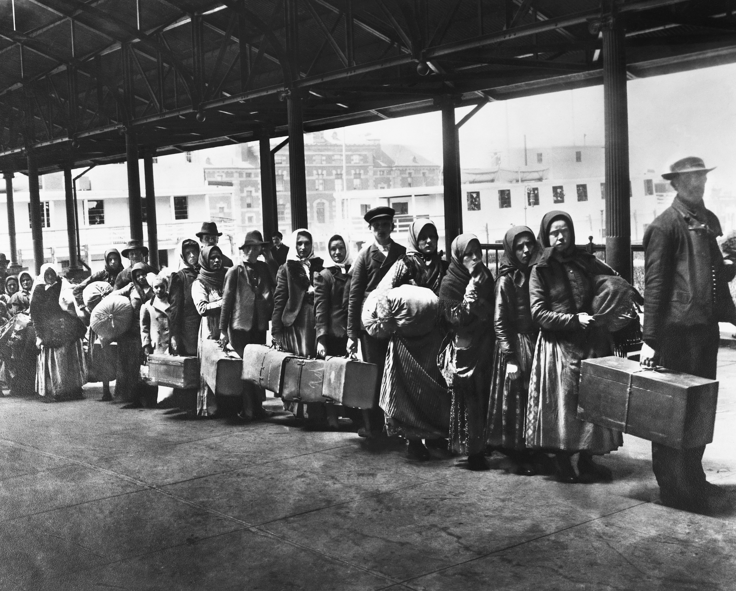 Immigrants on line leaving Ellis Island waiting for ferry to N.Y., ca 1900.