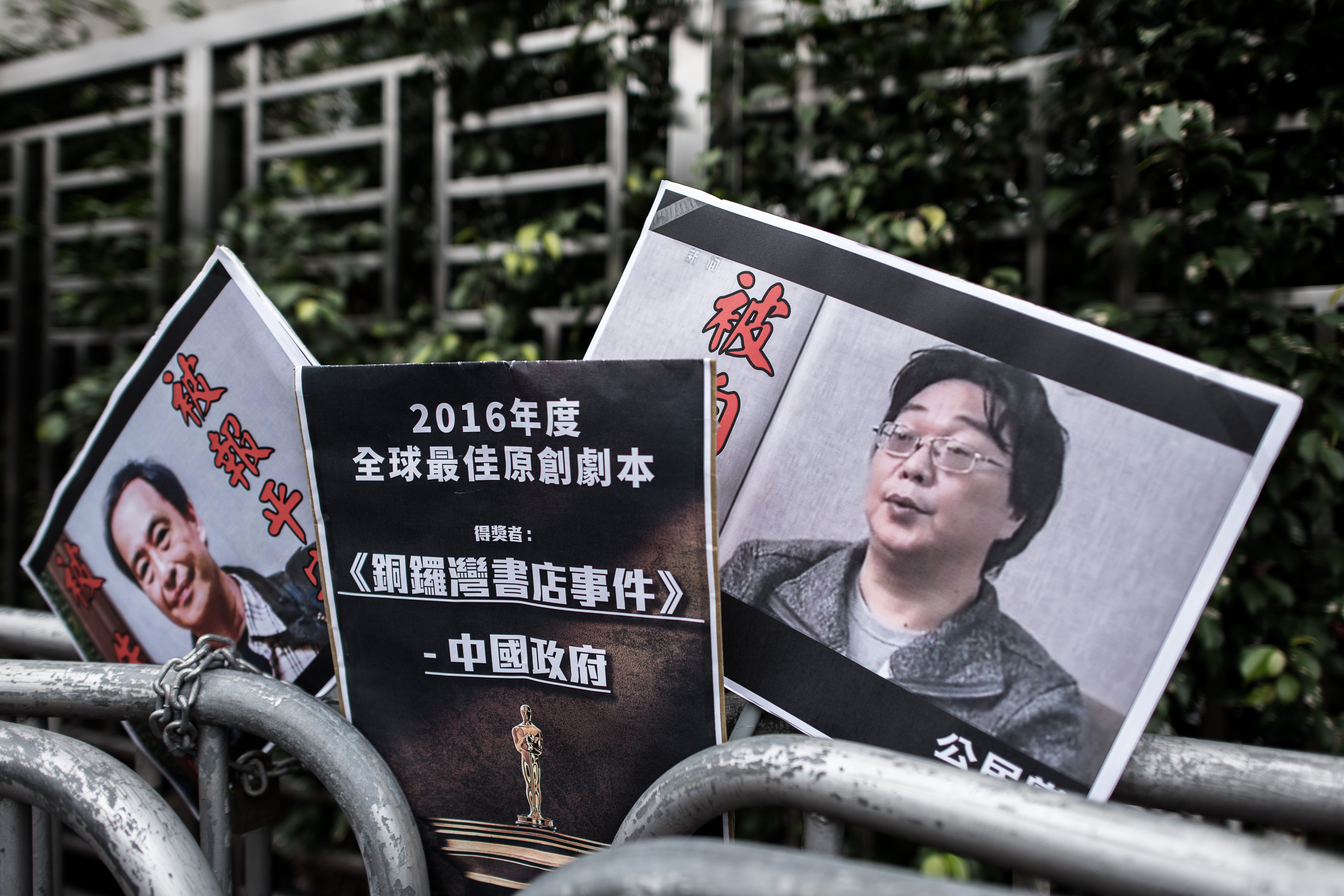 Placards showing missing bookseller Lee Bo (L) and his associate Gui Minhai (R) are seen outside the China liaison office in Hong Kong on January 19, 2016.