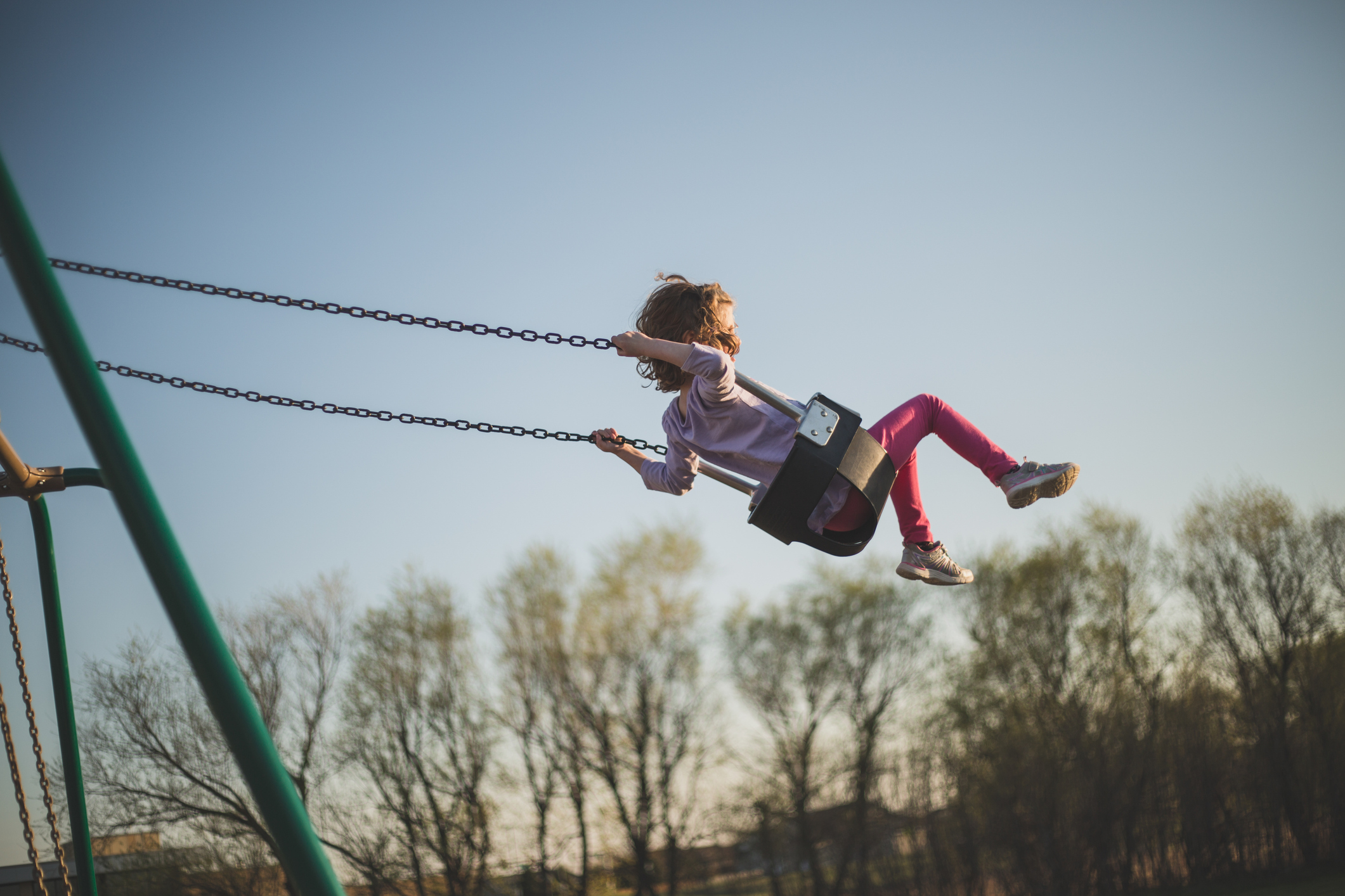 Little girl swings way up high into the sky above the trees on a swing set.