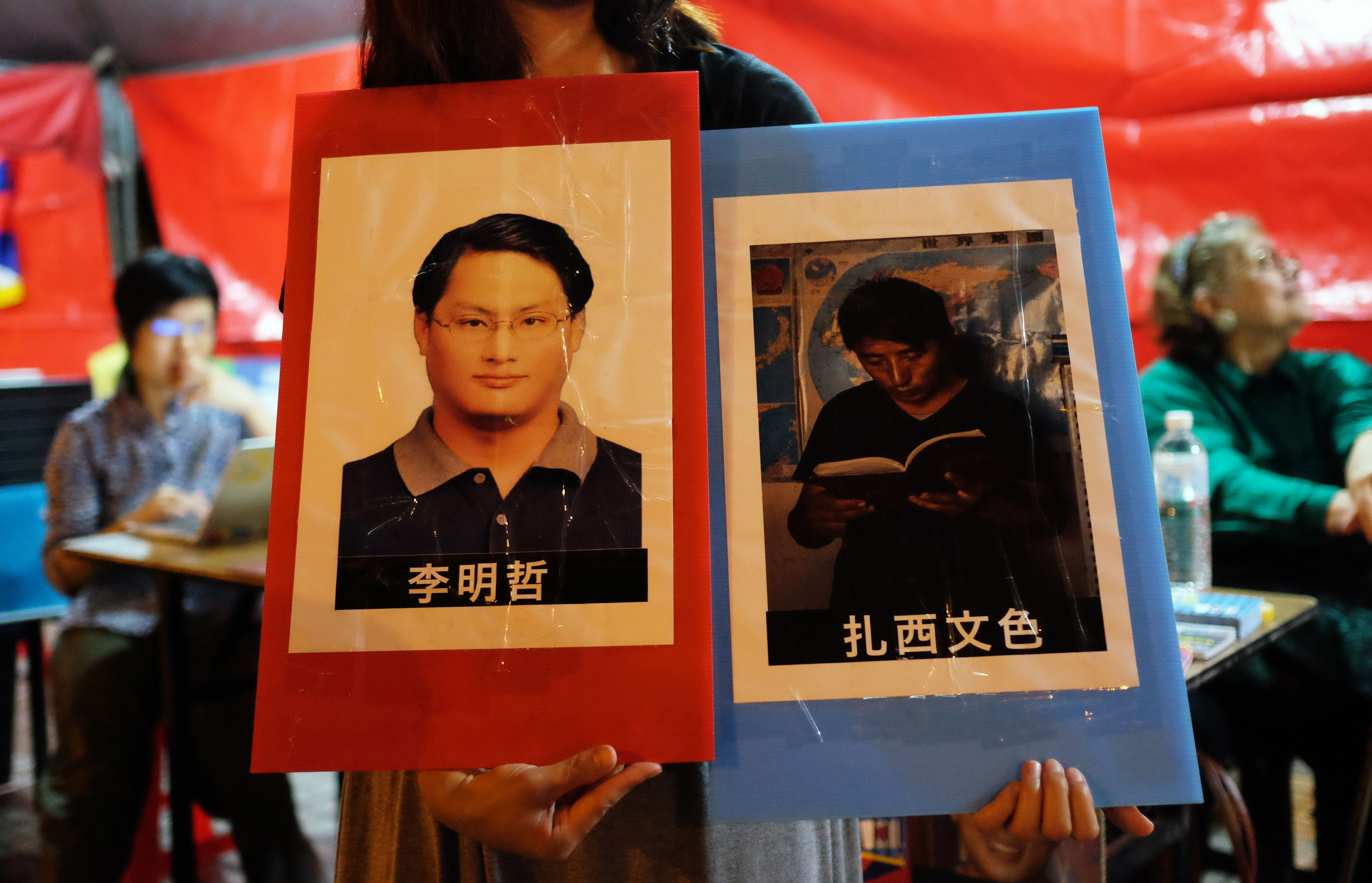 A volunteer holds placards of detained Tibetan activist Tashi Wangchuk and Taiwanese activist Lee Ming-cheh in Taipei, Taiwan on June 4, 2017.