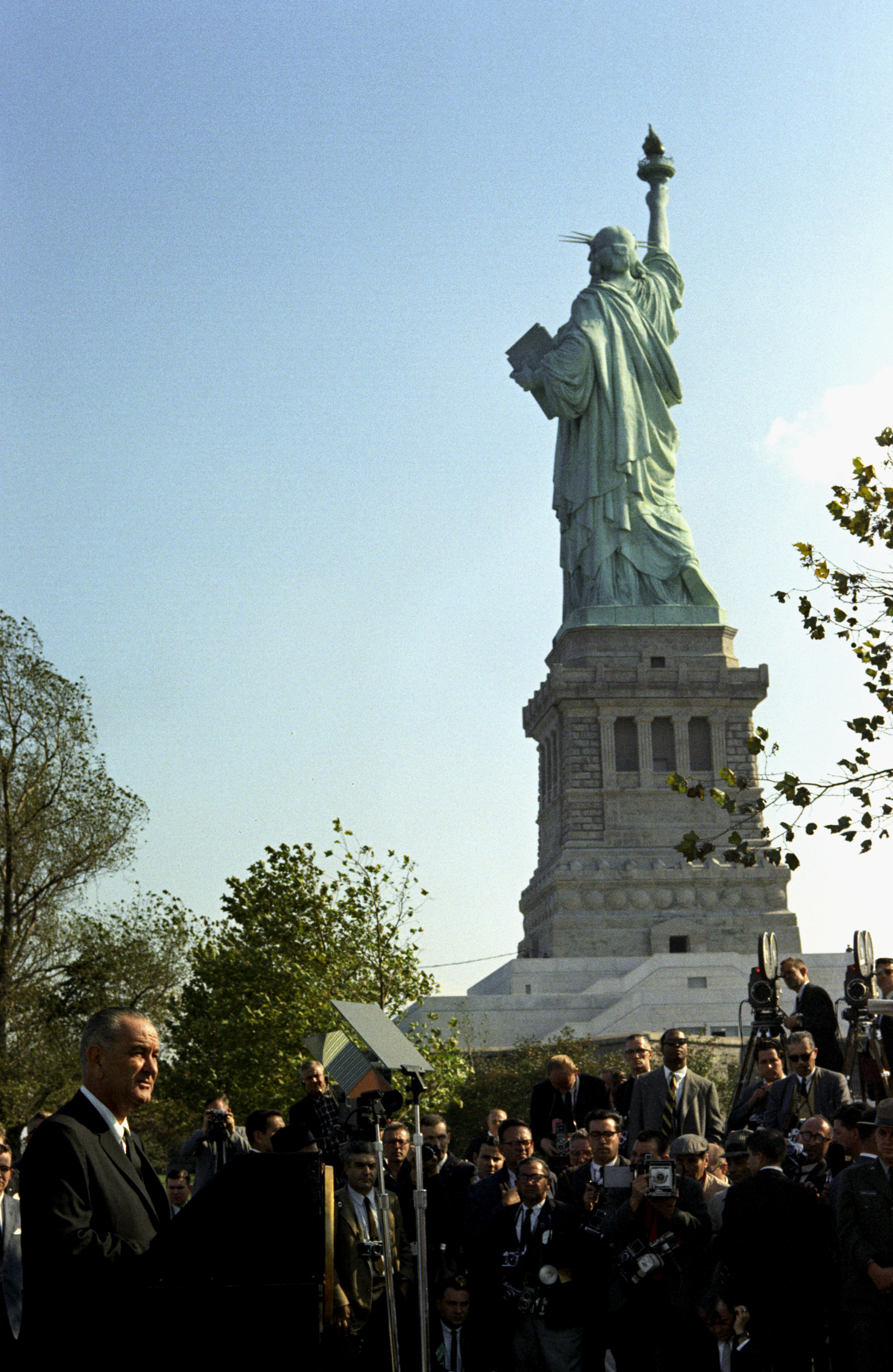 With the Statue of Liberty in the background, President Lyndon B Johnson addresses the crowds before the signing of the Immigration and Nationality Act on Liberty Island in New York, N.Y., on Oct. 3, 1965.