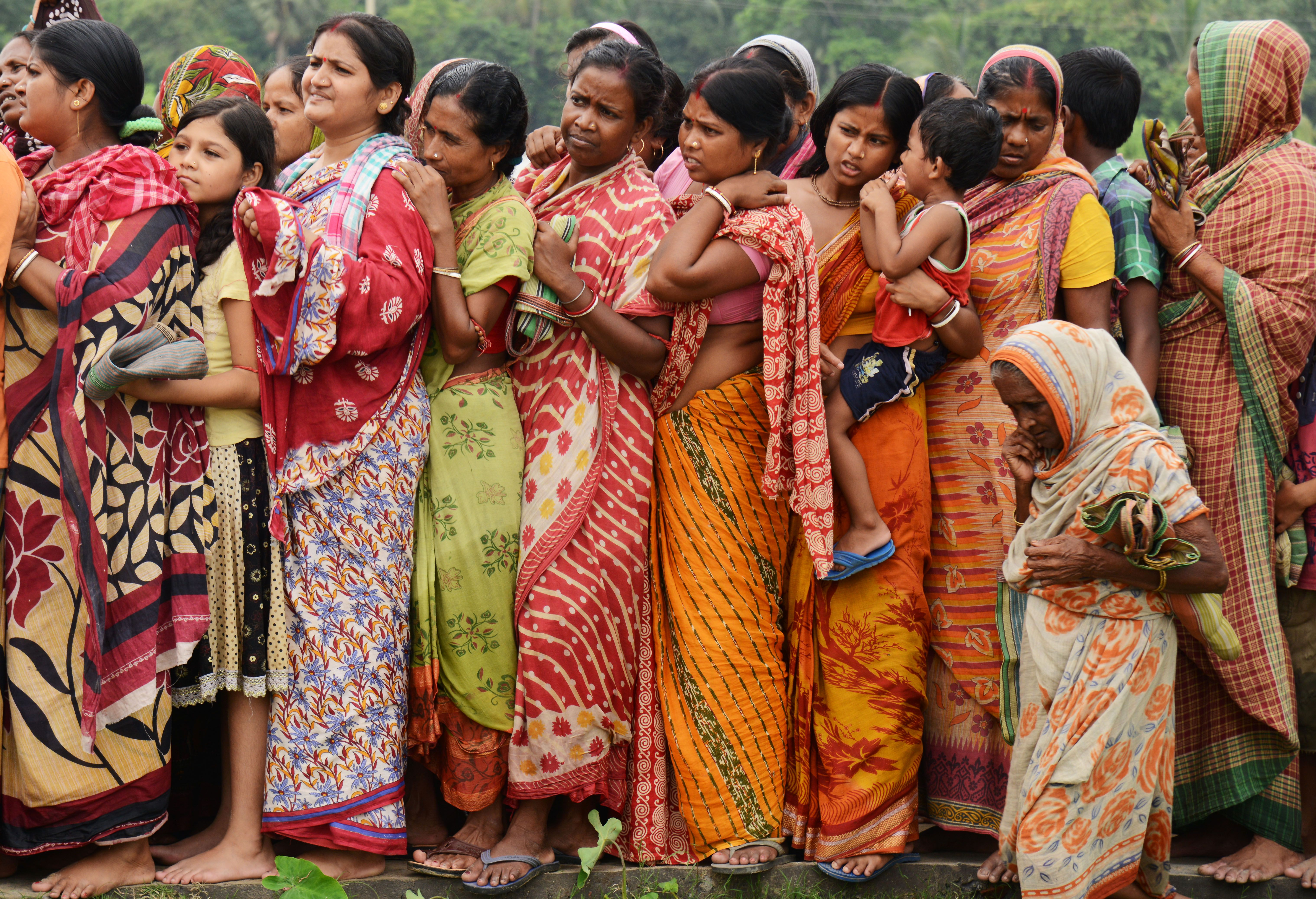 Indian flood victims wait in a queue to collect relief materials in Chitnan village, around 60 km West of Kolkata, on July 28, 2017.
