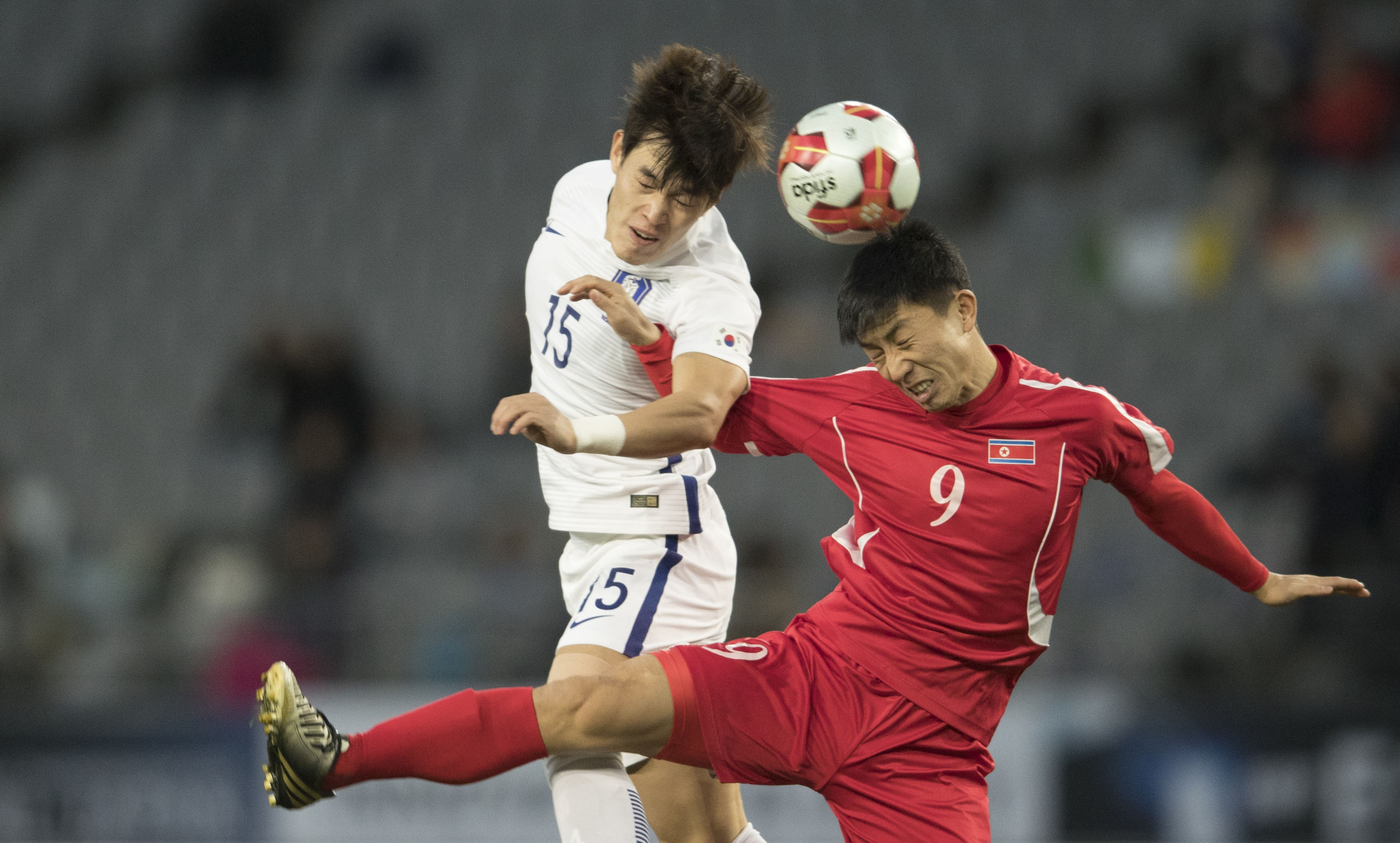 Pak Song Chol (#9) of North Korea and Lee changmin (#15) of South Korea in action during the EAFF E-1 Men's Football Championship at the Ajinomoto Stadium on December 12, 2017 in Chofu, Tokyo, Japan.