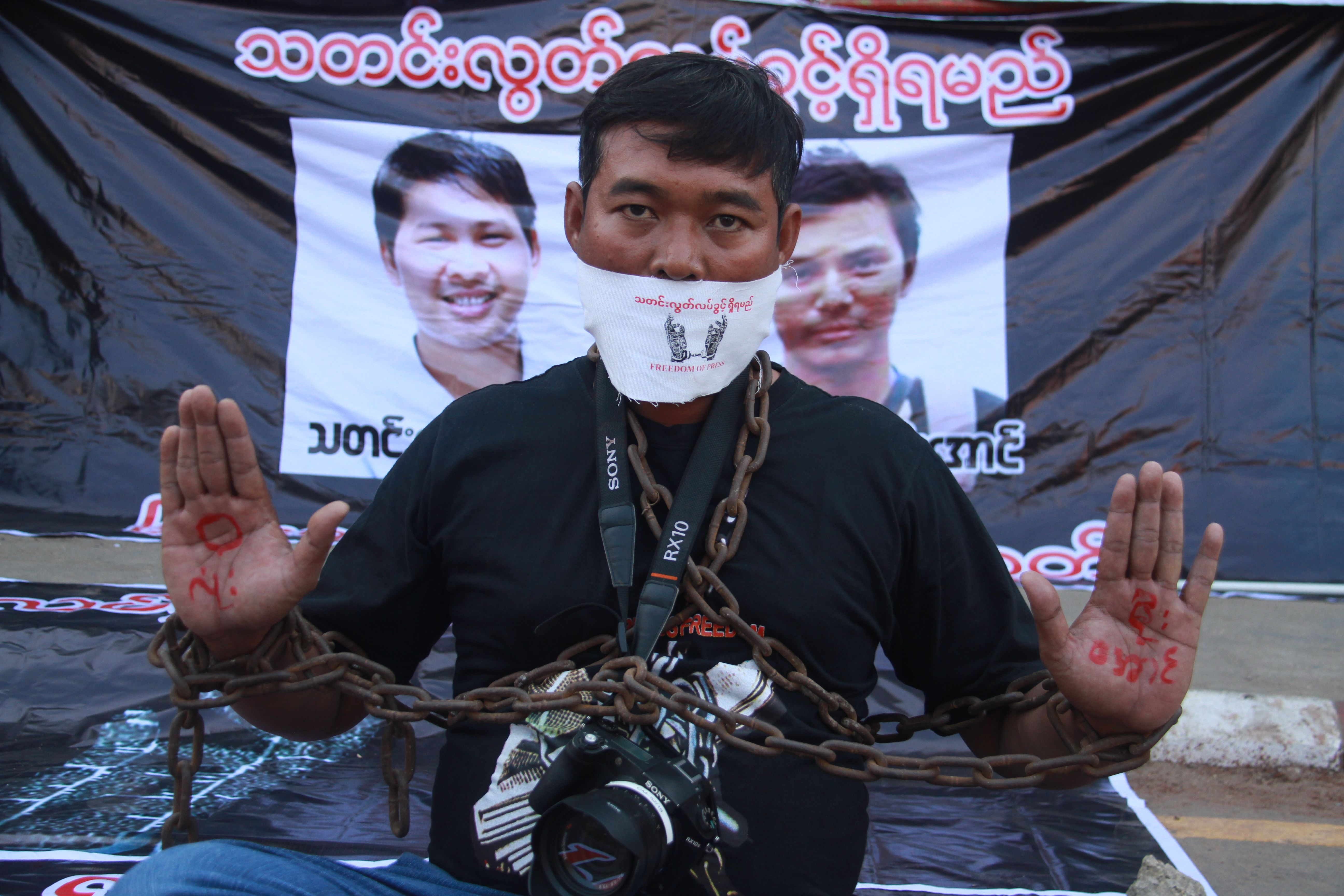 A journalist protests the arrest of Reuters journalists Wa Lone and Kyaw Soe Oo (pictured in posters behind) in Pyay, Myanmar on Dec. 27, 2017.