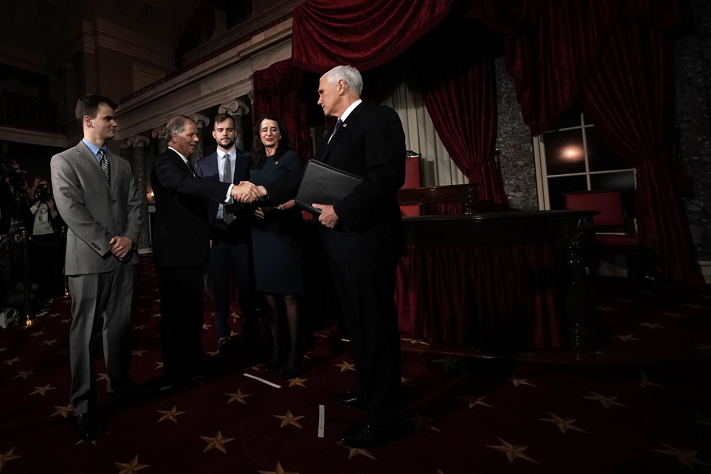 U.S. Sen. Doug Jones (D-AL) (2nd L) shakes hands with Vice President Mike Pence (R) as Jones' wife Louise (4th L), sons Carson (3rd L) and Christopher (L) look on during a mock swearing-in ceremony   at the Old Senate Chamber of the U.S. Capitol January 3, 2018 in Washington, DC. Jones is the first Democratic senator from Alabama in more than two decades. He defeated Roy Moore leaving Republicans with a 51-49 majority in the U.S. Senate.  Alex Wong—Getty Images
