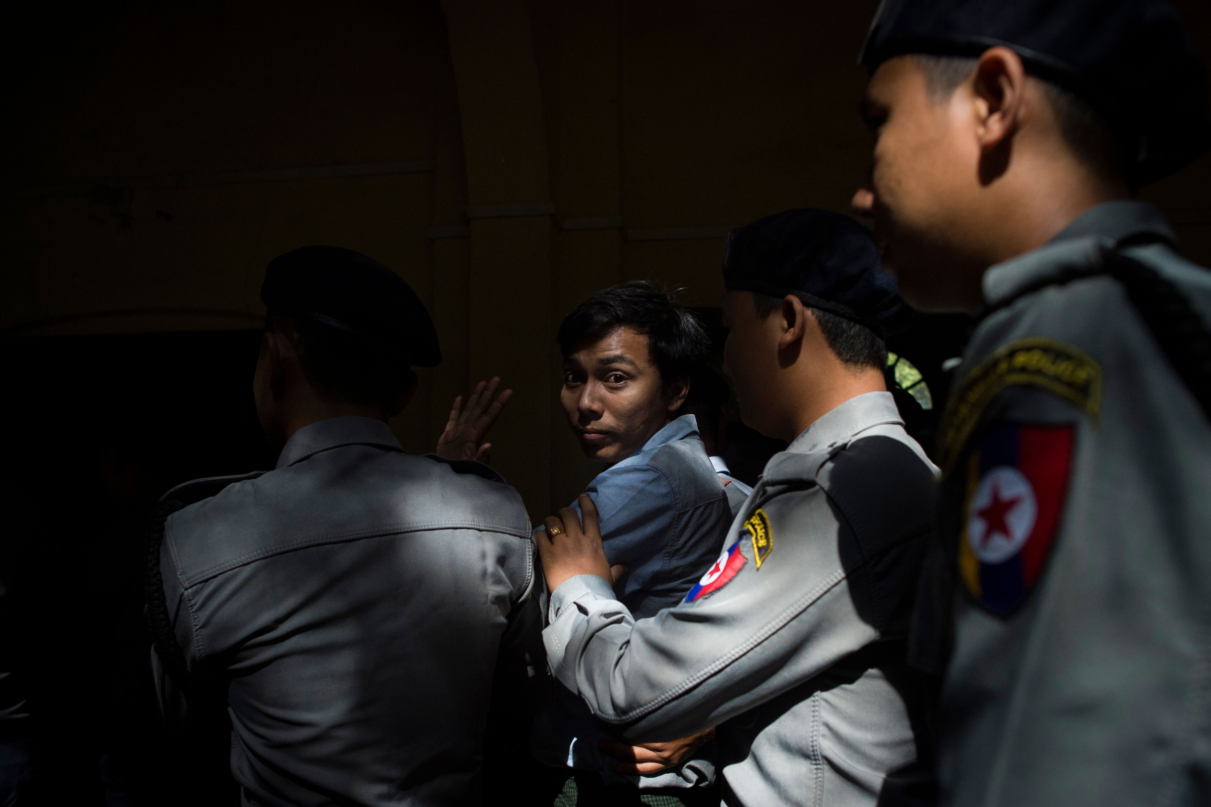 Reuters journalist Kyaw Soe Oo is escorted by police after a court appearance in Yangon, Myanmar on Jan. 10, 2018.