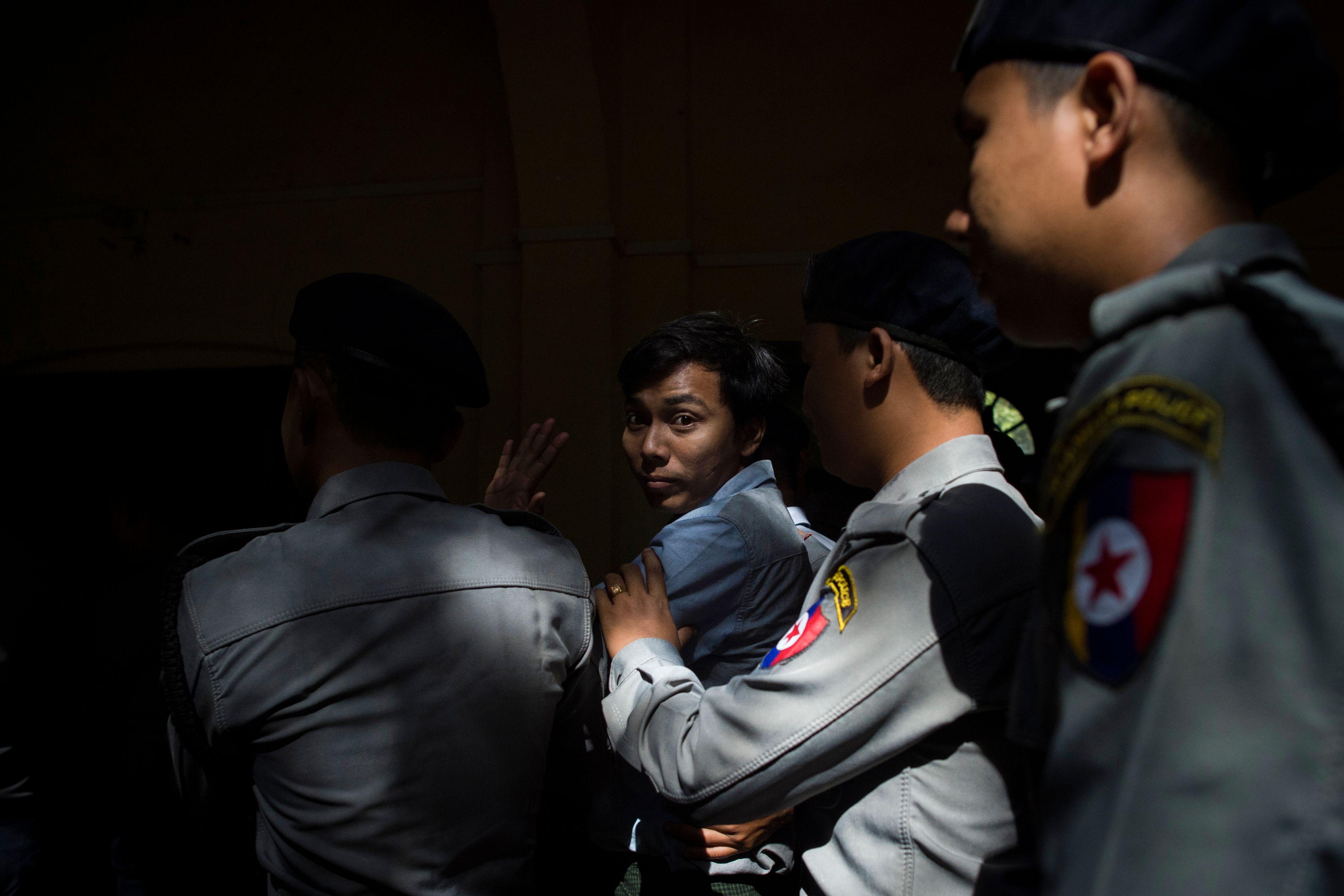 Reuters journalist Kyaw Soe Oo is escorted by police after a court appearance in Yangon, Myanmar on Jan. 10, 2018.