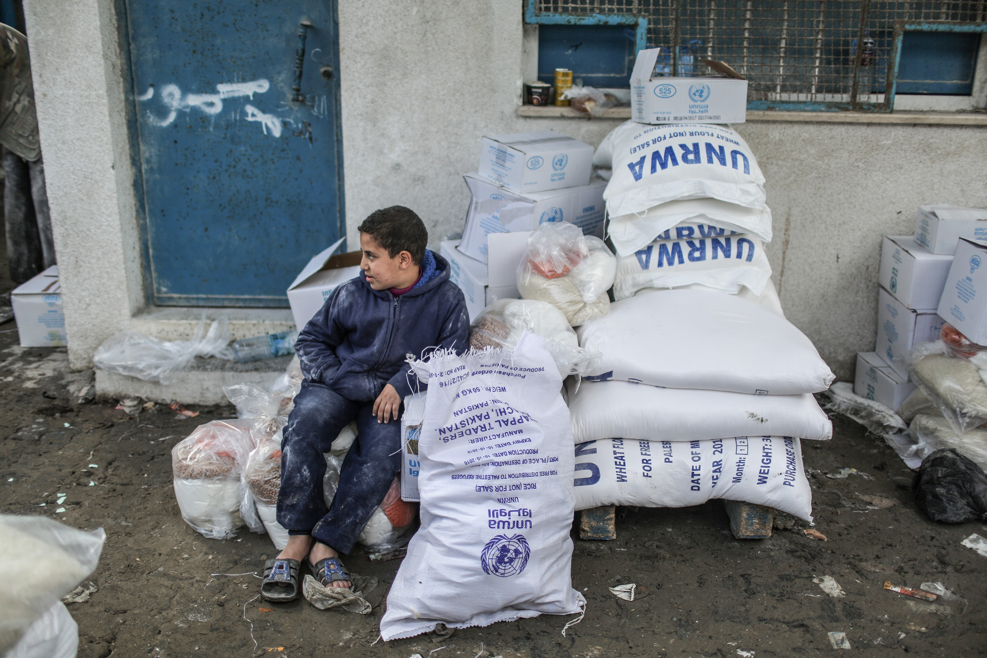 A boy sits near sacks of flour during a food aid distribution by the United Nations Relief and Works Agency for Palestine Refugees in the Near East (UNRWA) at Al-Shati Refugee Camp in Gaza City, Gaza on January 15, 2018.