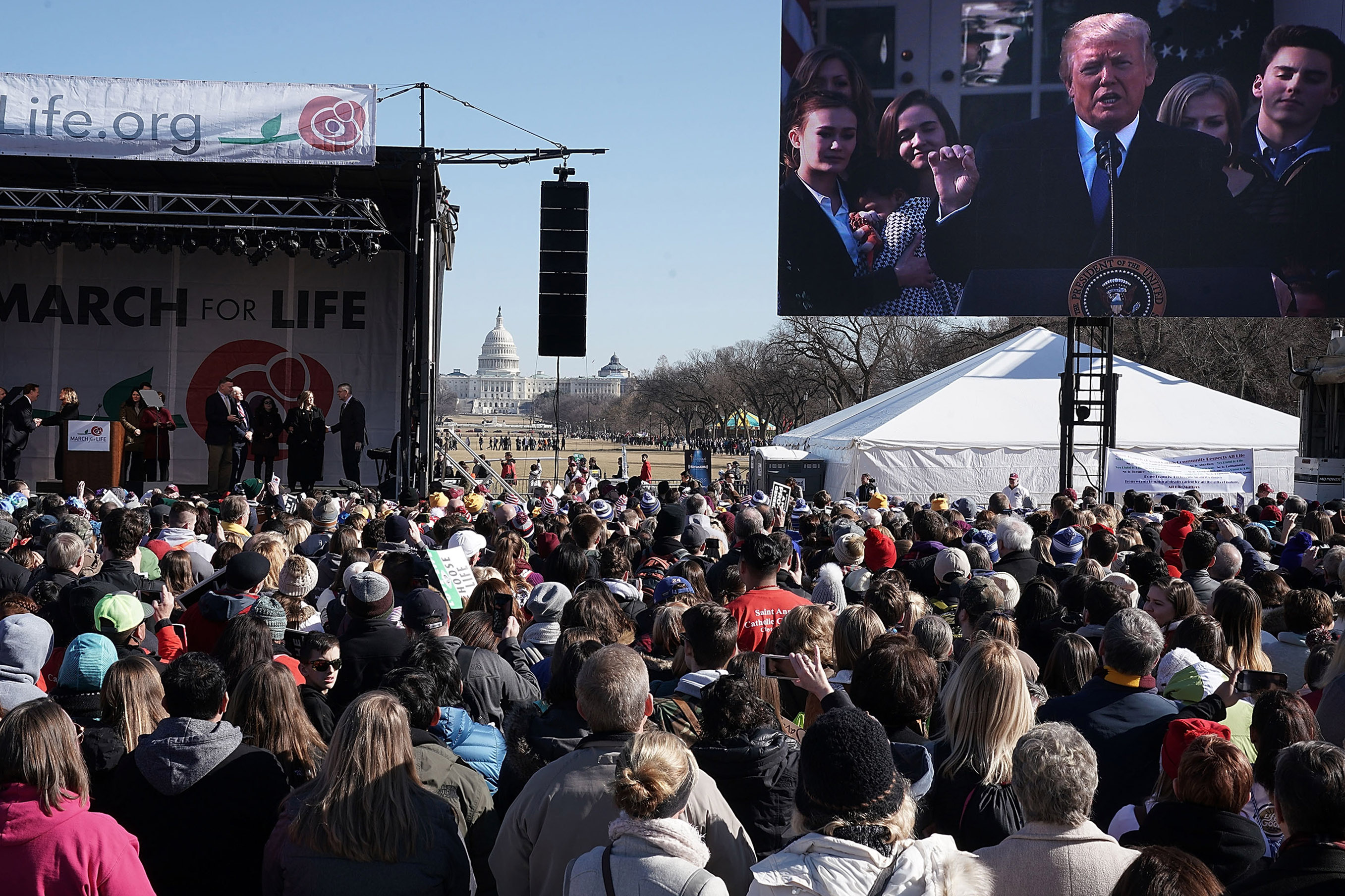 Pro-life activists watch U.S. President Donald Trump giving remarks from the Rose Garden of the White House on a jumbotron during a rally at the National Mall prior to the 2018 March for Life on Jan. 19, 2018, in Washington, DC