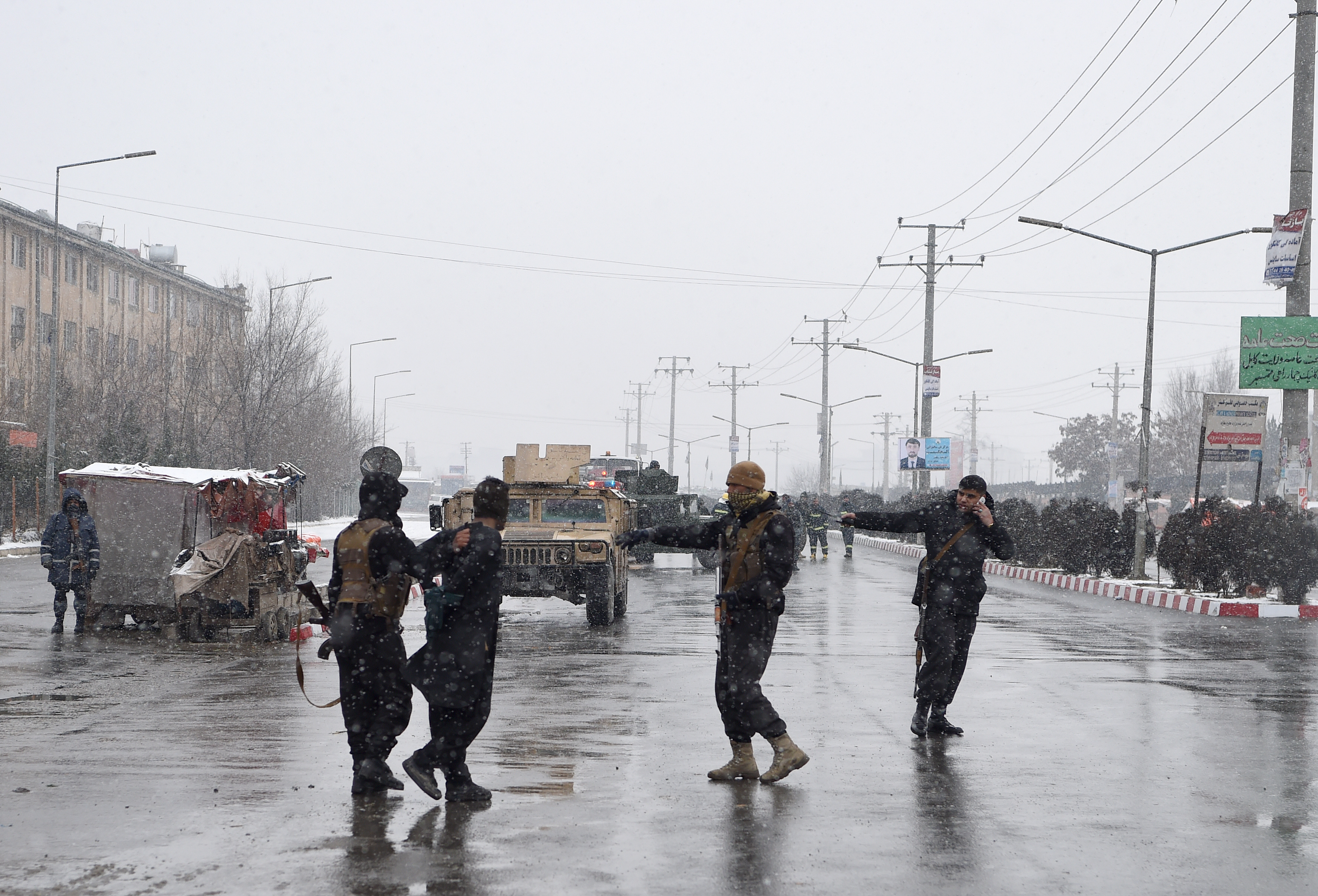 Afghan security personnel detain a suspect as they guard the site of an attack near the Marshal Fahim Military Academy base in Kabul on January 29, 2018.