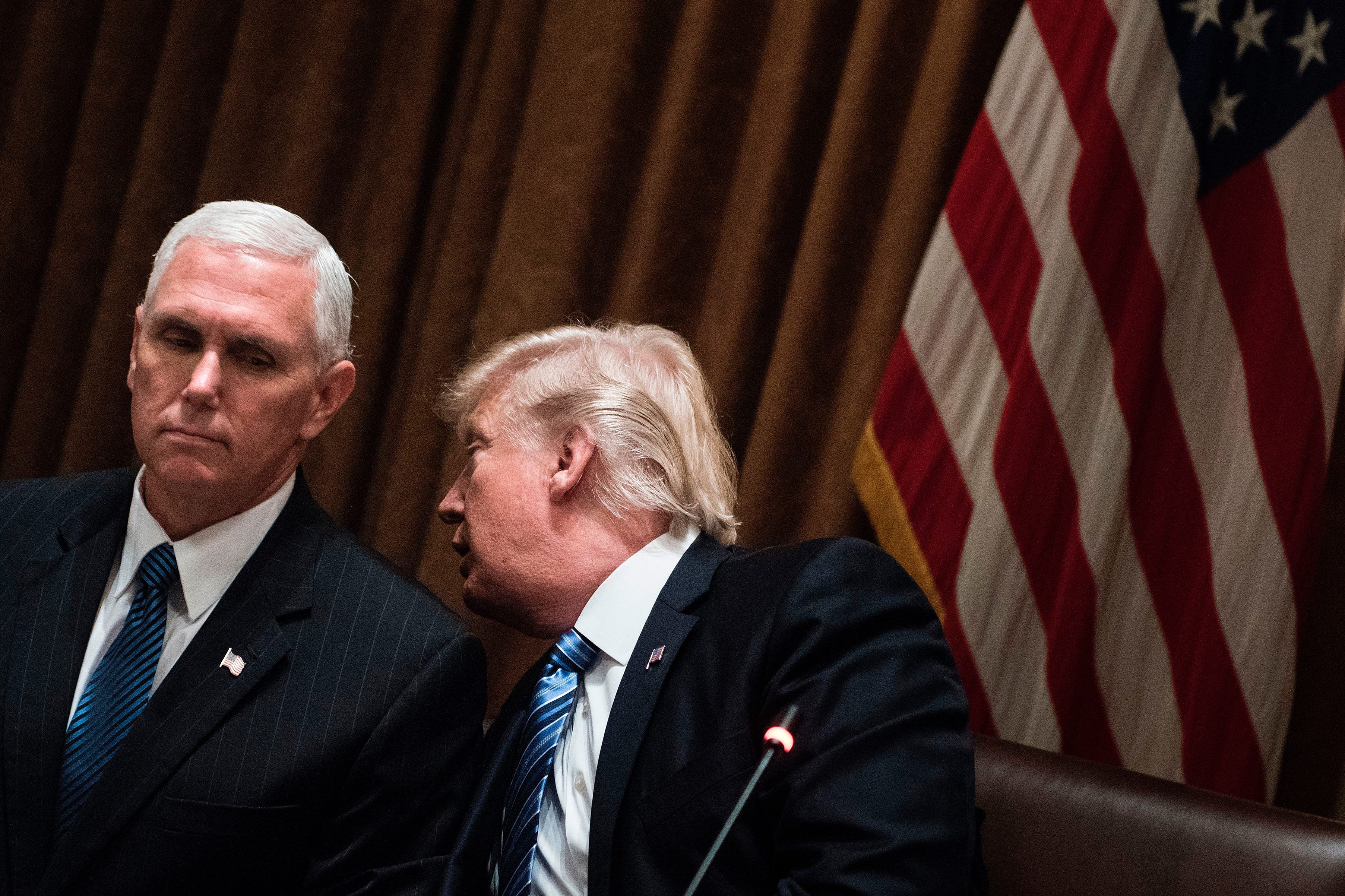 US President Donald Trump whispers to US Vice President Mike Pence before a meeting with South Korea's President Moon Jae-in in the Cabinet Room of the White House June 30, 2017 in Washington, DC.