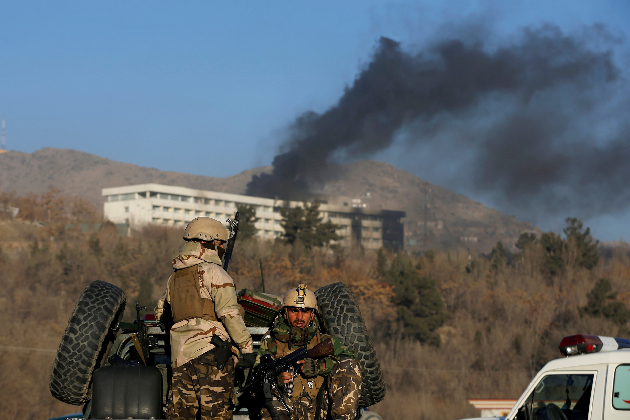 Afghan security forces keep watch as smoke rises from the Intercontinental Hotel in Kabul, Afghanistan on Jan. 21, 2018.