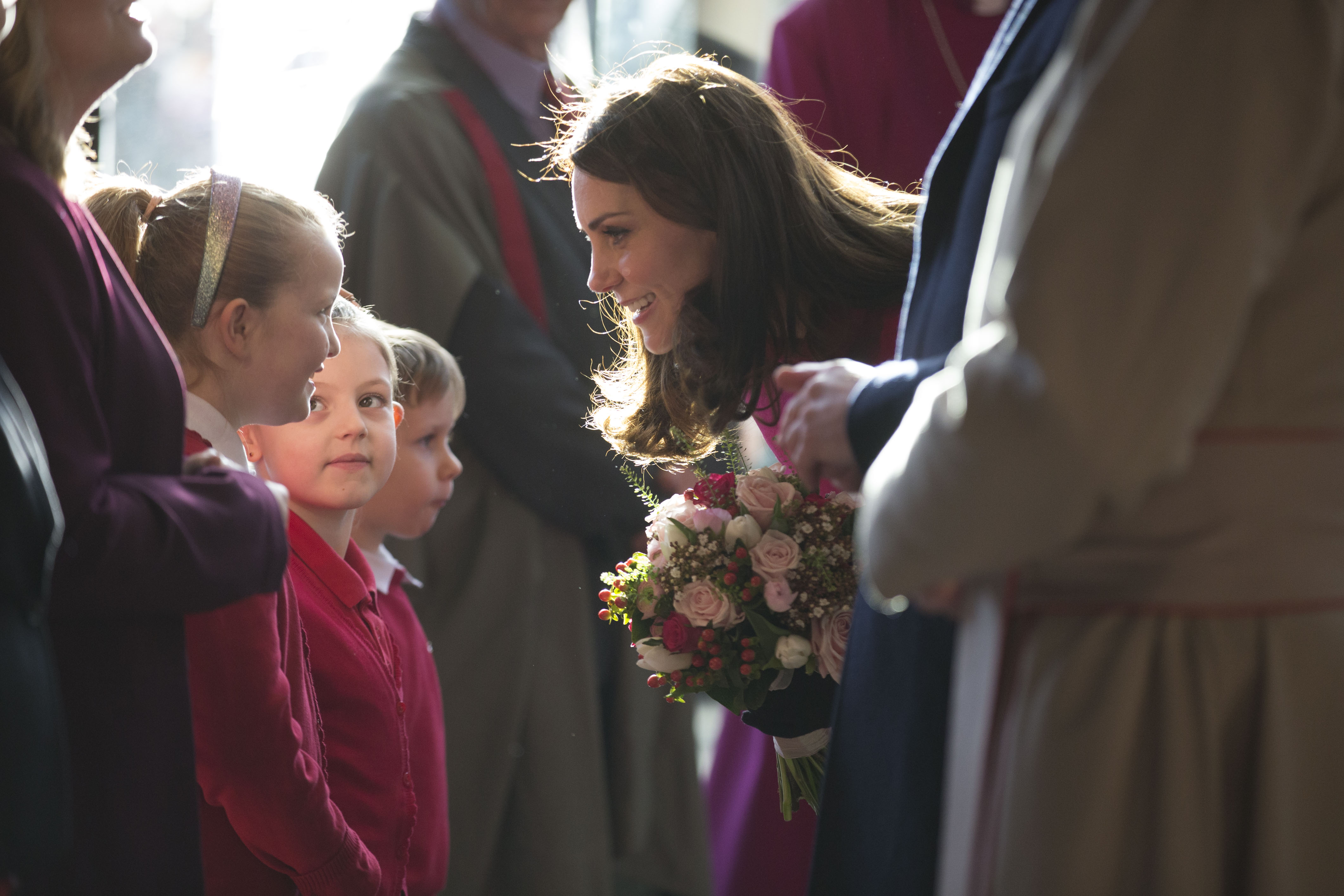 Catherine, Duchess of Cambridge receives flowers from Megan (aged 7), Isabella (aged 8) and Szymek (aged 7) from Coundon Primary School at Coventry Cathedral during her visit to the city on January 16, 2018 in Coventry, England.