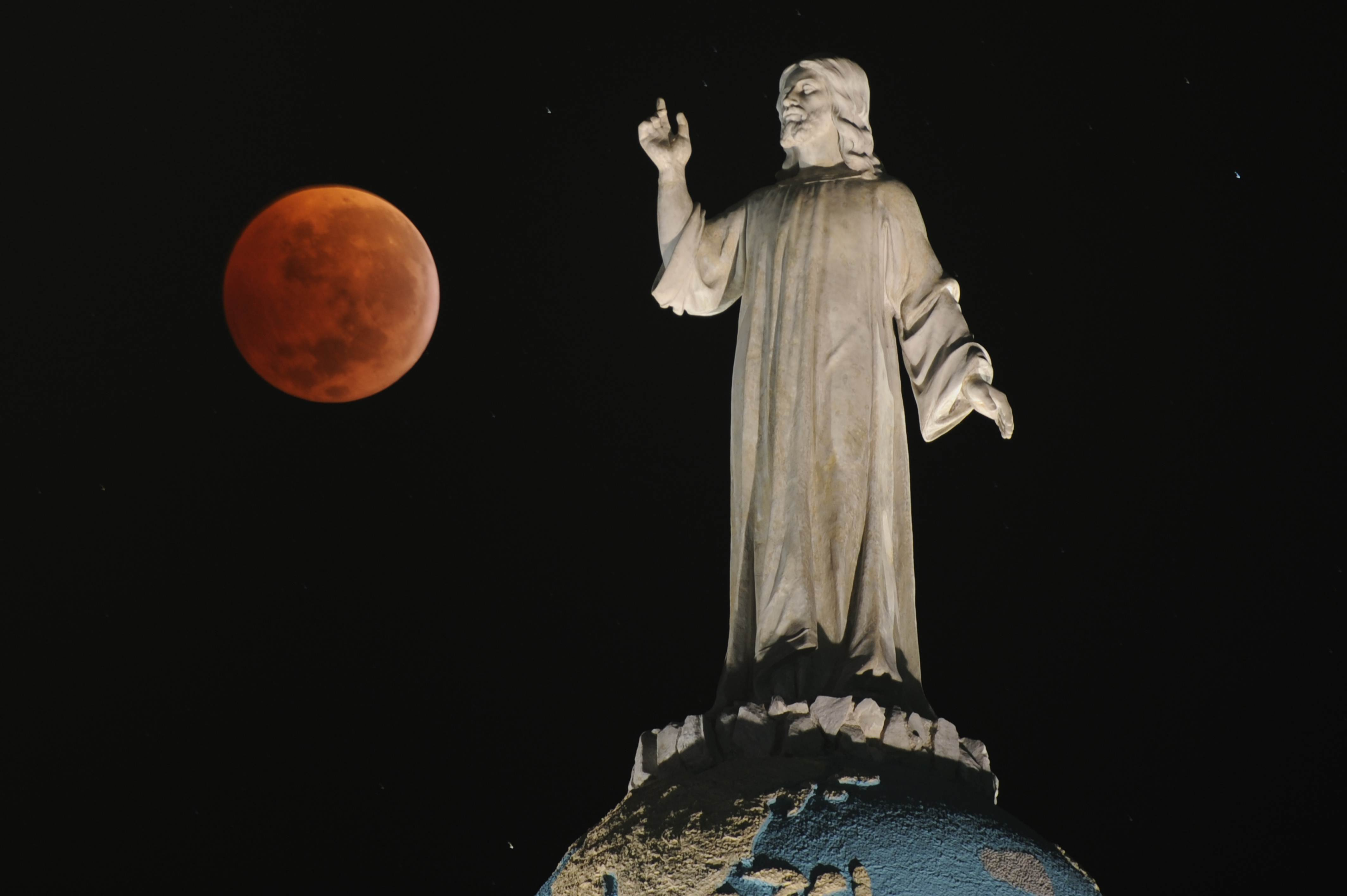 A double exposure picture shows the moon and the monument of The Savior of The World during a total lunar eclipse as seen from San Salvador, El Salvador on December 21, 2010.
