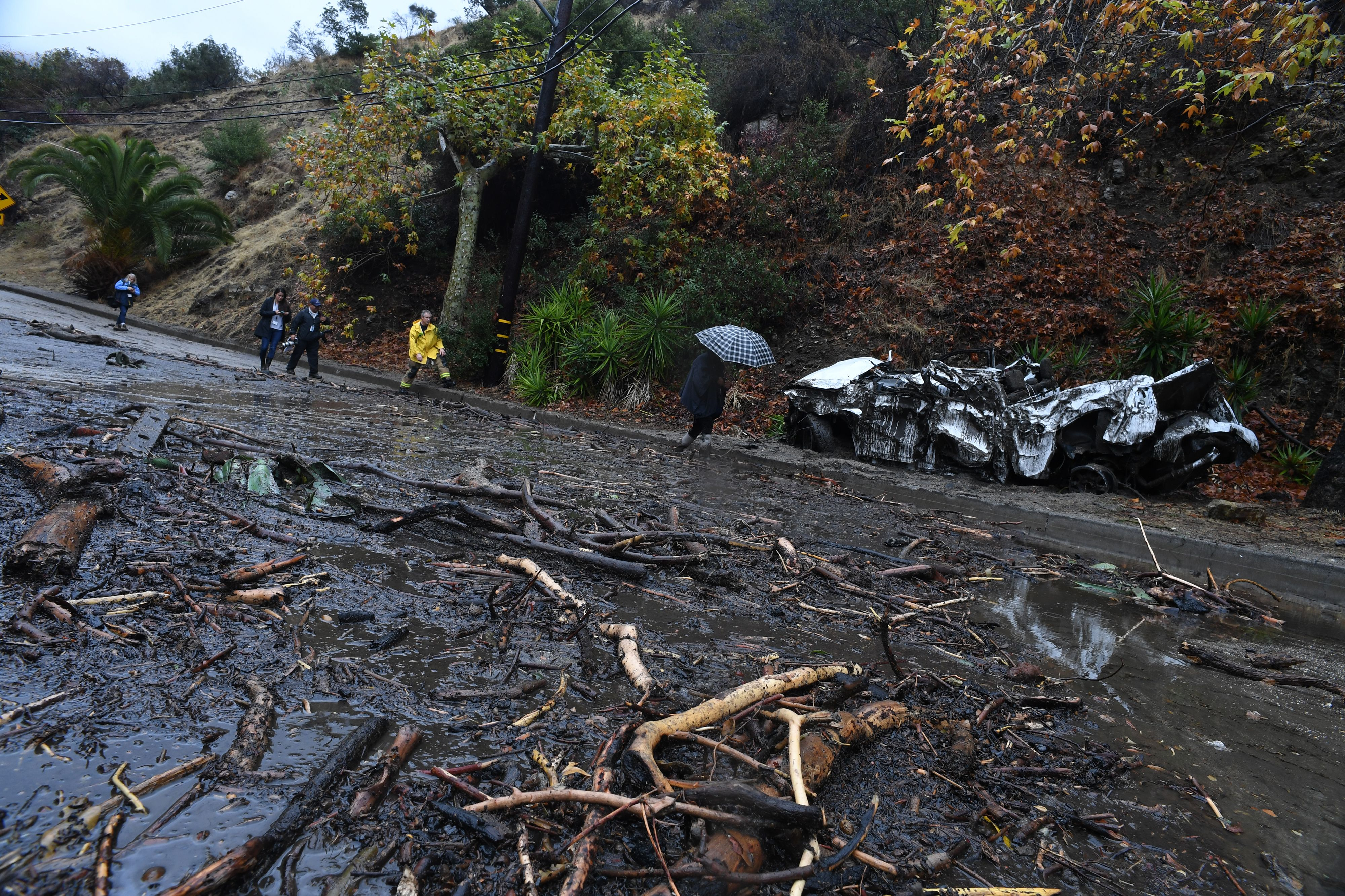 A firefighter (in yellow) instructs journalists to retreat to safer ground after a rain-driven mudslide destroyed two cars and damaged property in a neighborhood under mandatory evacuation in Burbank, California, January 9, 2018.