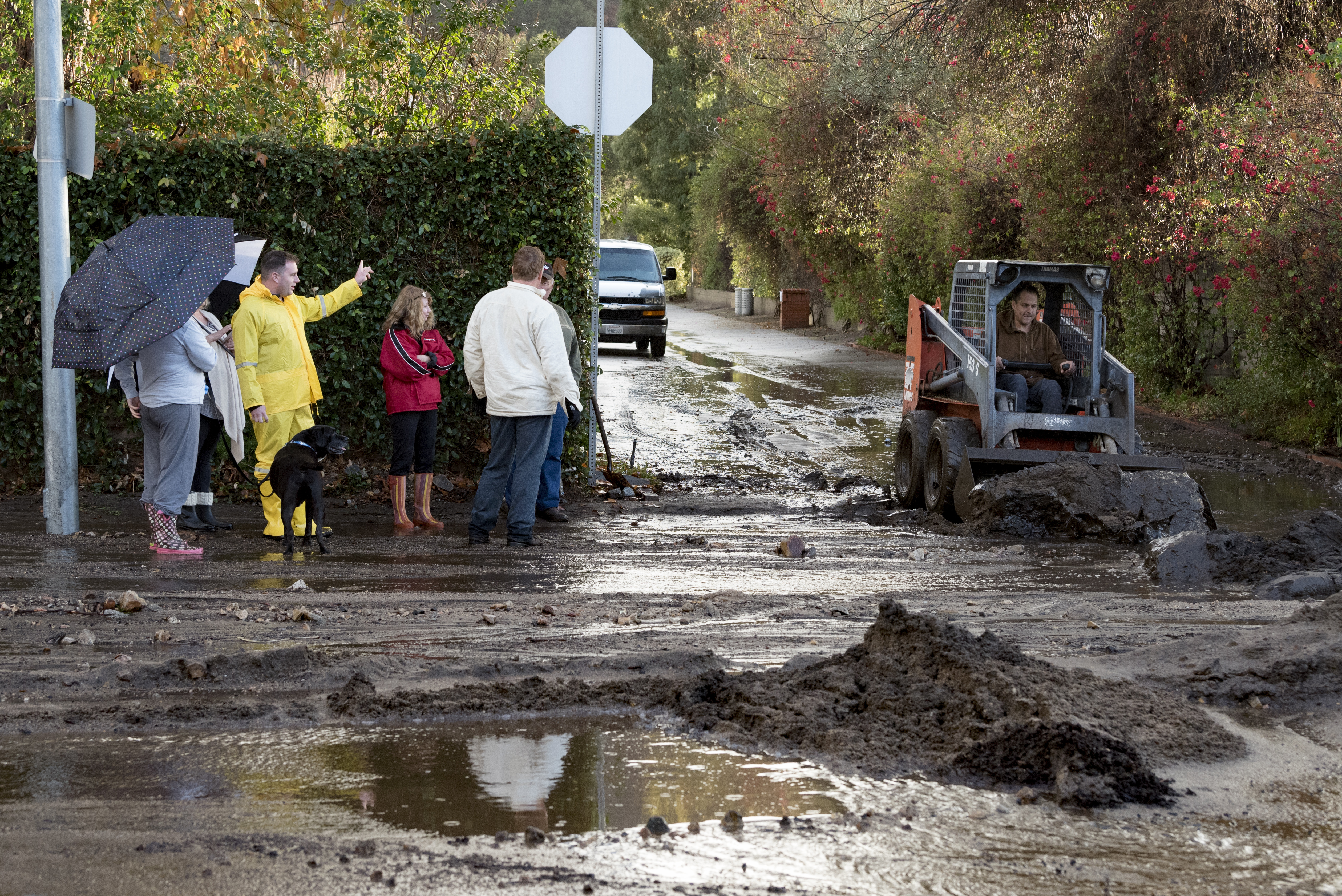 Residents look on as a man clears debris from a mudslide in Los Angeles, California on January 9, 2018. The deadly storm claimed the lives of 13 people in Santa Barbara County. Flash flooding also occurred in the recently burned areas of Ventura and Los Angeles counties.