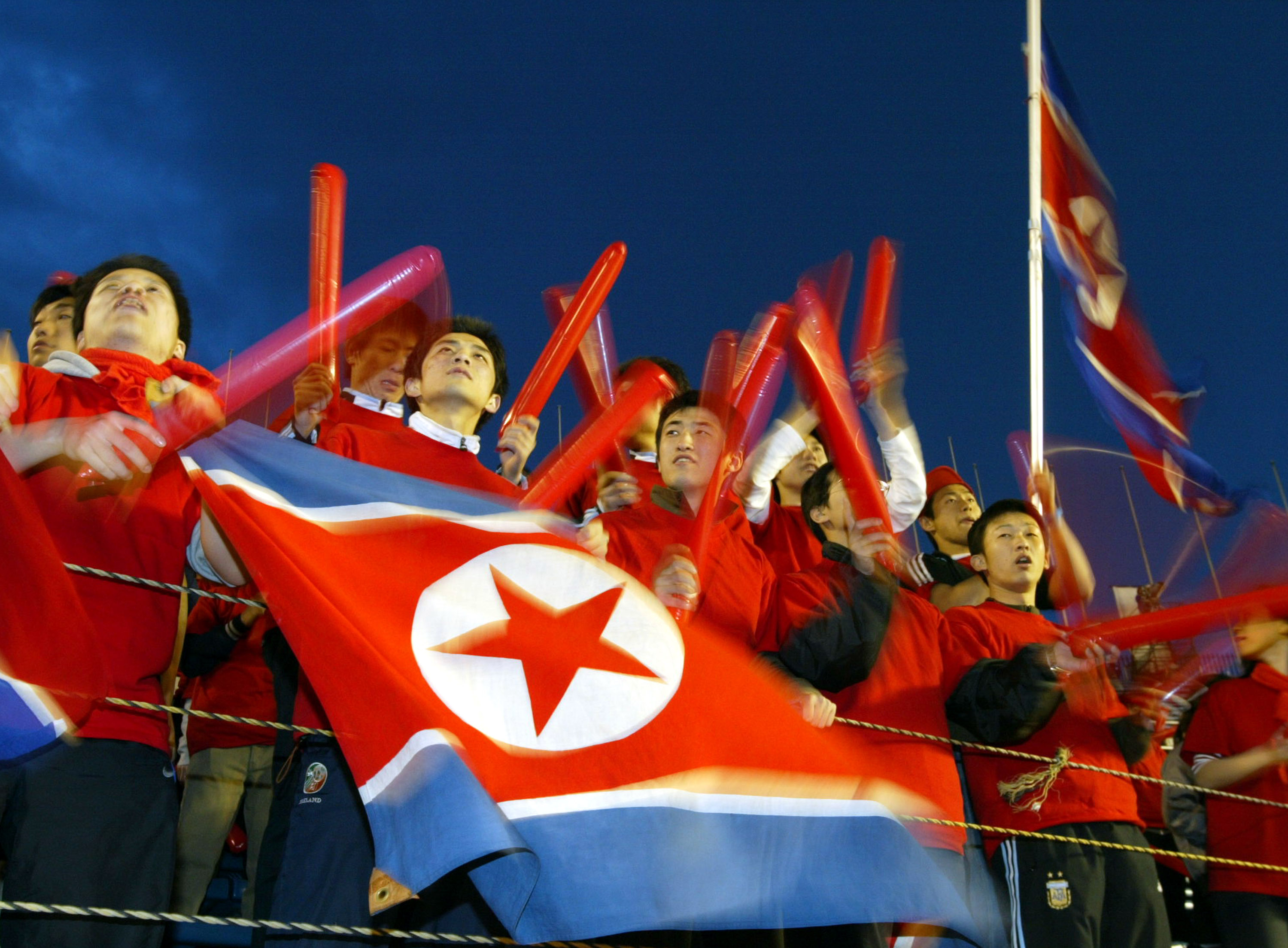 Fans of the North Korean national women's soccer team, cheer at the AFC Olympics qualifying tournament semi-final game against Japan at the National Stadium April 24, 2004 in Tokyo, Japan.